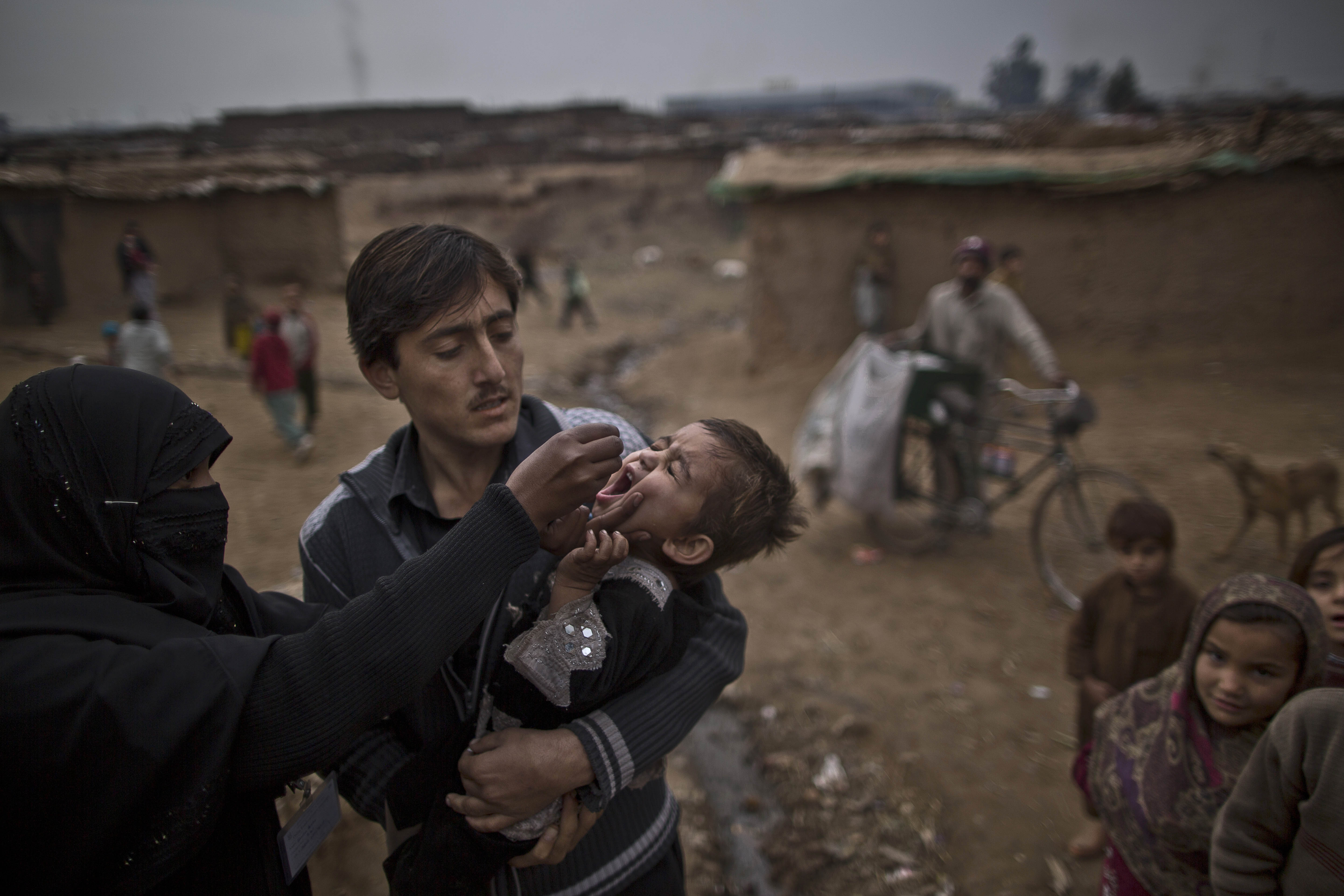 A Pakistani health worker, left, gives a polio vaccine to a child in a poor neighborhood that hosts people displaced from tribal areas and Afghan refugees, on the outskirts of Islamabad, Pakistan, Jan. 22, 2014.