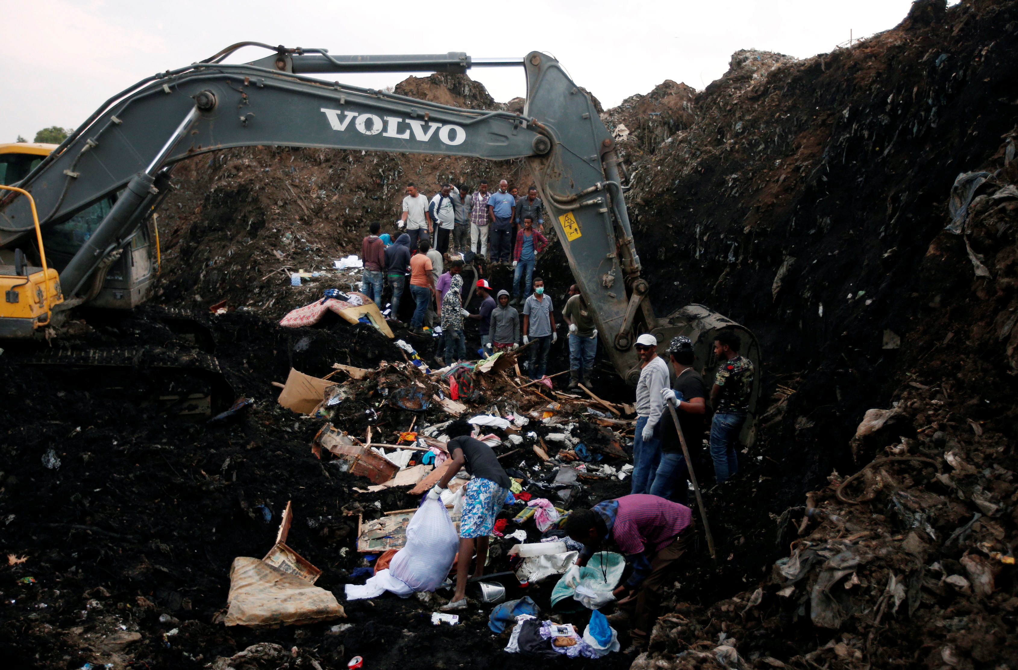 Rescue workers watch as excavators dig into a pile of garbage in search of missing people following a landslide when a mound of trash collapsed on an informal settlement at the Koshe garbage dump in Ethiopia's capital Addis Ababa, March 13, 2017.