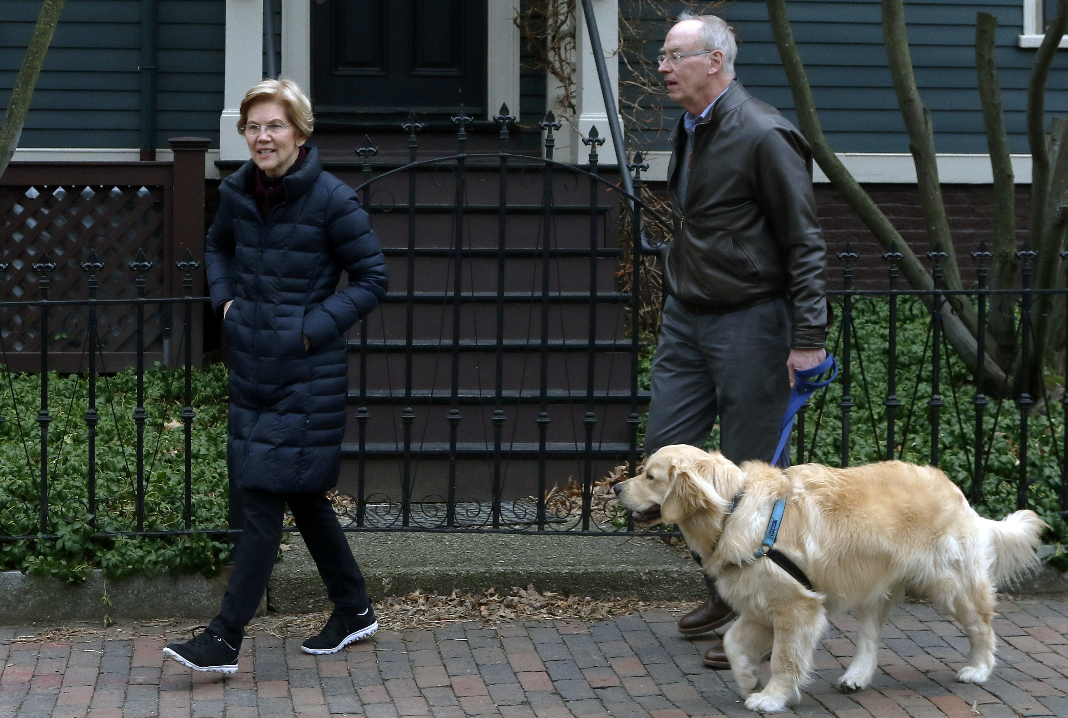 Democratic Sen. Elizabeth Warren steps outside her home with her husband Bruce Mann, right, and their retriever Bailey, Dec. 31, 2018, in Cambridge, Massachusetts, where she confirmed that she is launching an exploratory committee to run for presiden...
