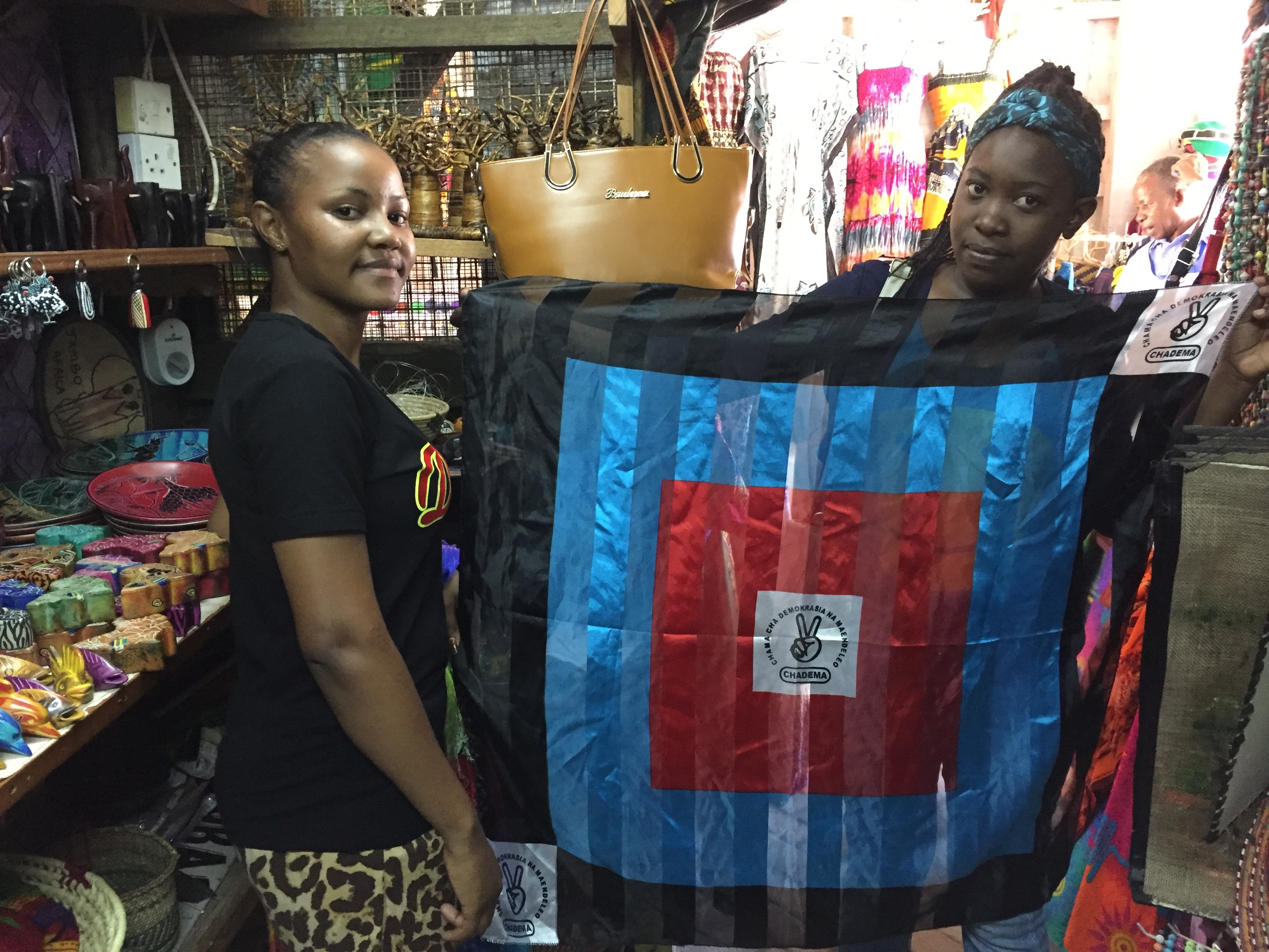 Chadema supporters show their party flag in a curio shop in Dar es Salaam, Oct. 24, 2015. (Jill Craig/VOA)