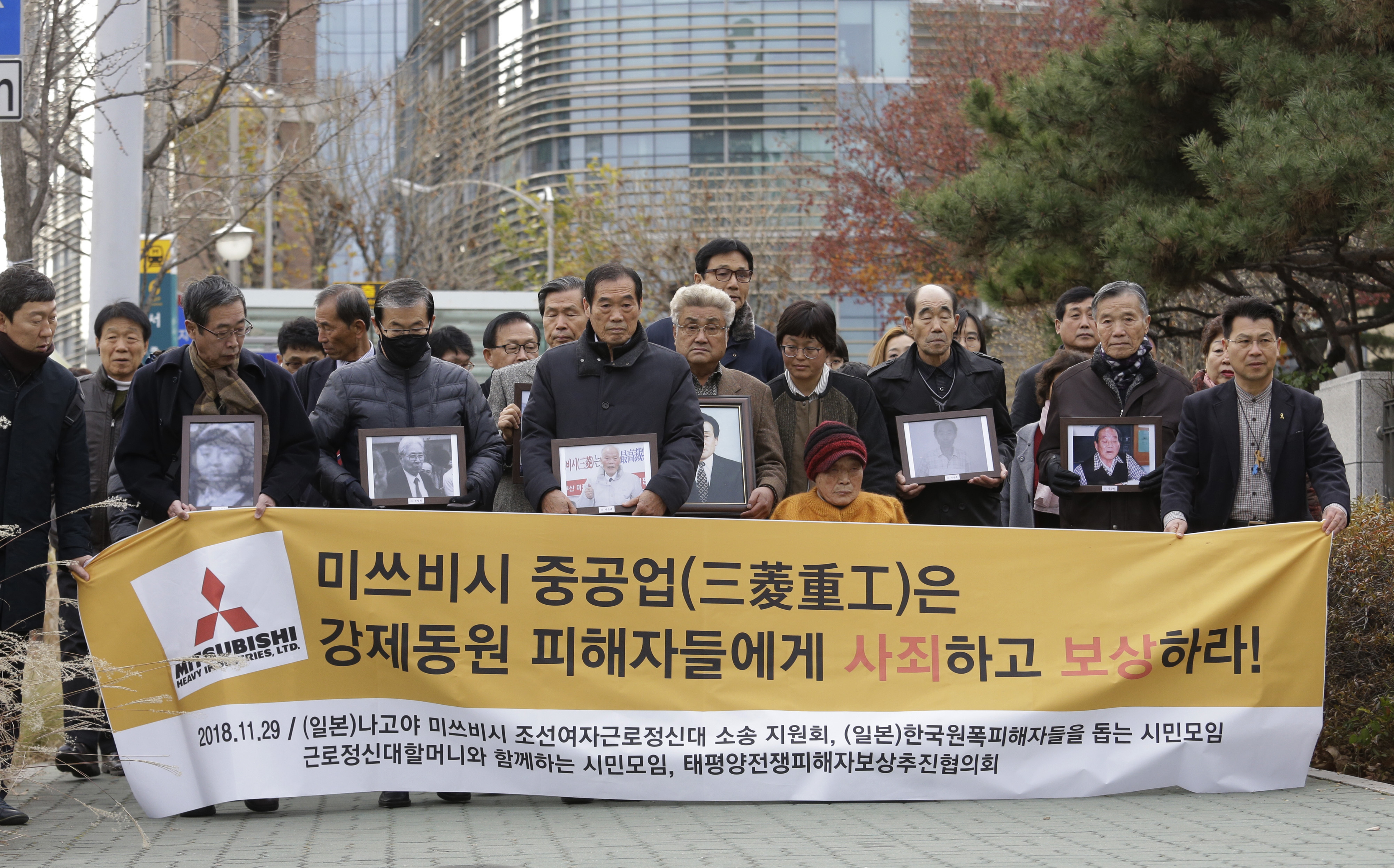 """Victims of Japan's forced labor and their family members arrive at the Supreme Court in Seoul, South Korea, Nov. 29, 2018. The sign reads """" Mitsubishi Heavy Industries apologize and compensate victims."""""""