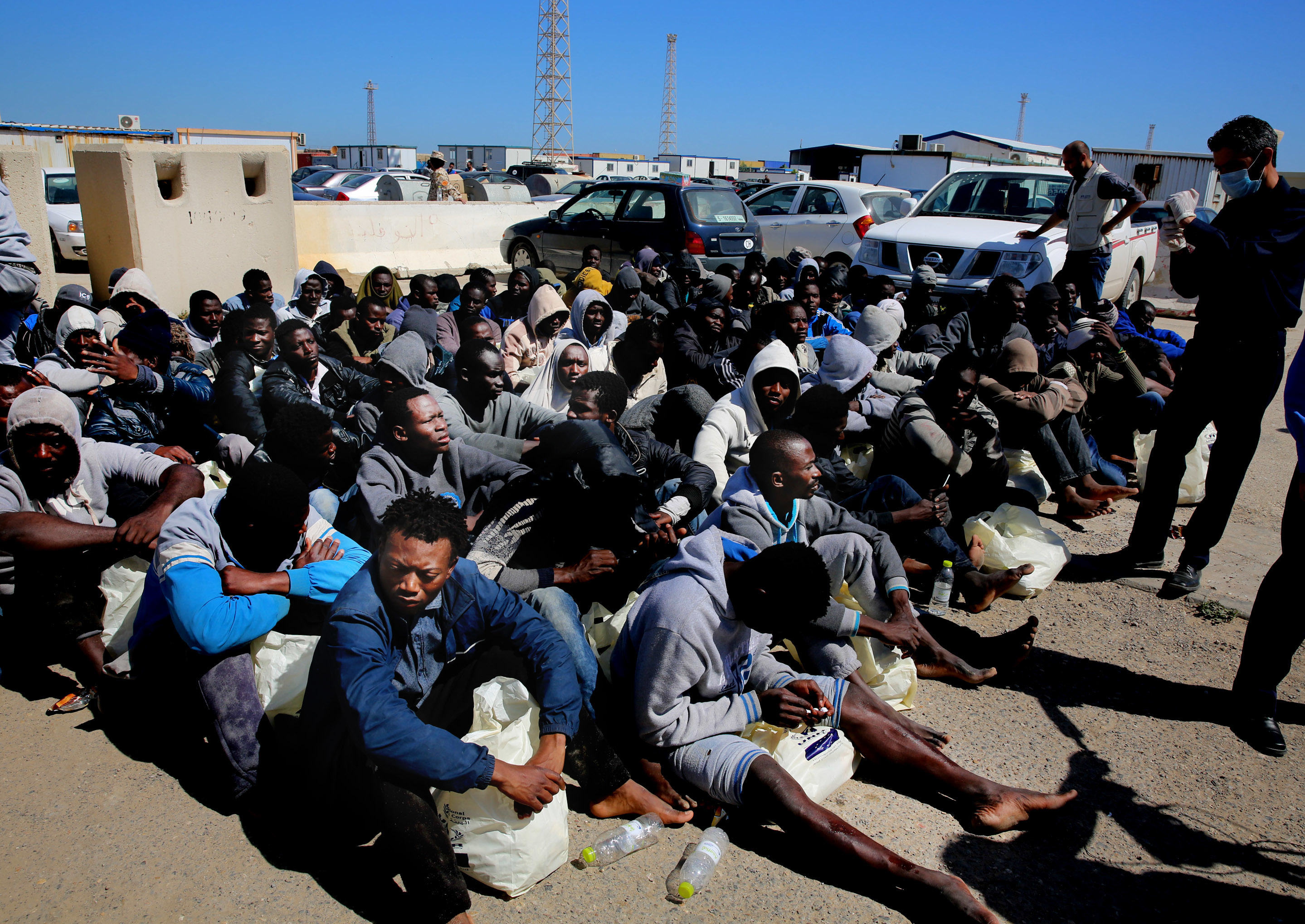 African illegal migrants wait to receive medial assistance after being rescued by coast guards, in Tripoli, Libya, April 11, 2016. More than 100 migrants were rescued by two coastal guards on Monday after their boat started sinking in the sea.