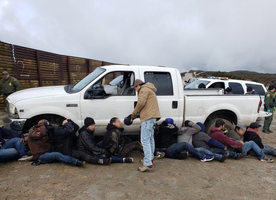 FILE - Border patrol agents detain suspects following an incident in which a truck smashed through the border wall in east San Diego, California, U.S., in this Feb. 21, 2019 handout photo. (CBP San Diego via social media)