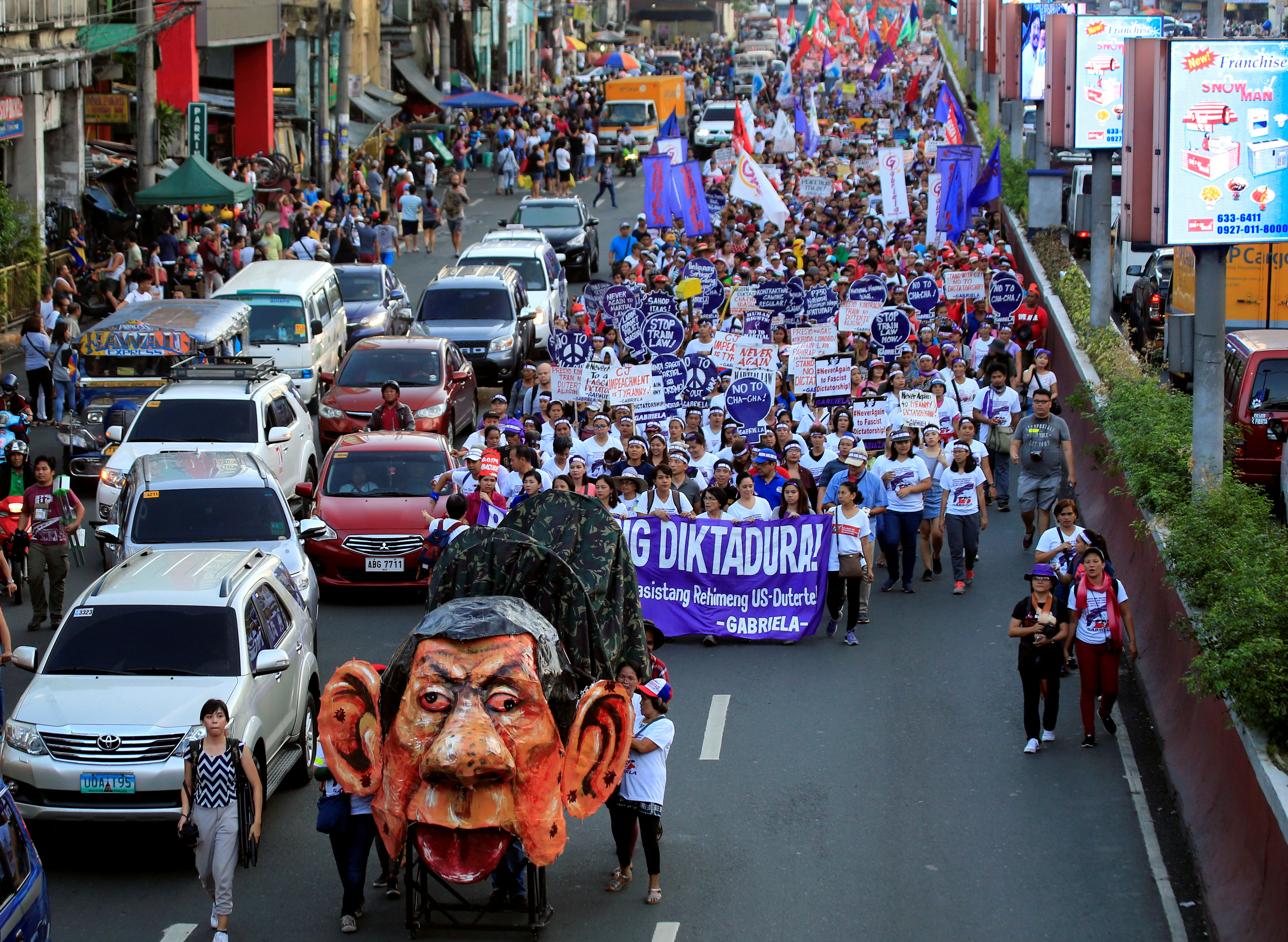An effigy of Philippine President Rodrigo Duterte is seen while women's rights activists march along a busy street during a celebration of the International Women's Day in Quiapo city, Metro Manila, Philippines, March 8, 2018.