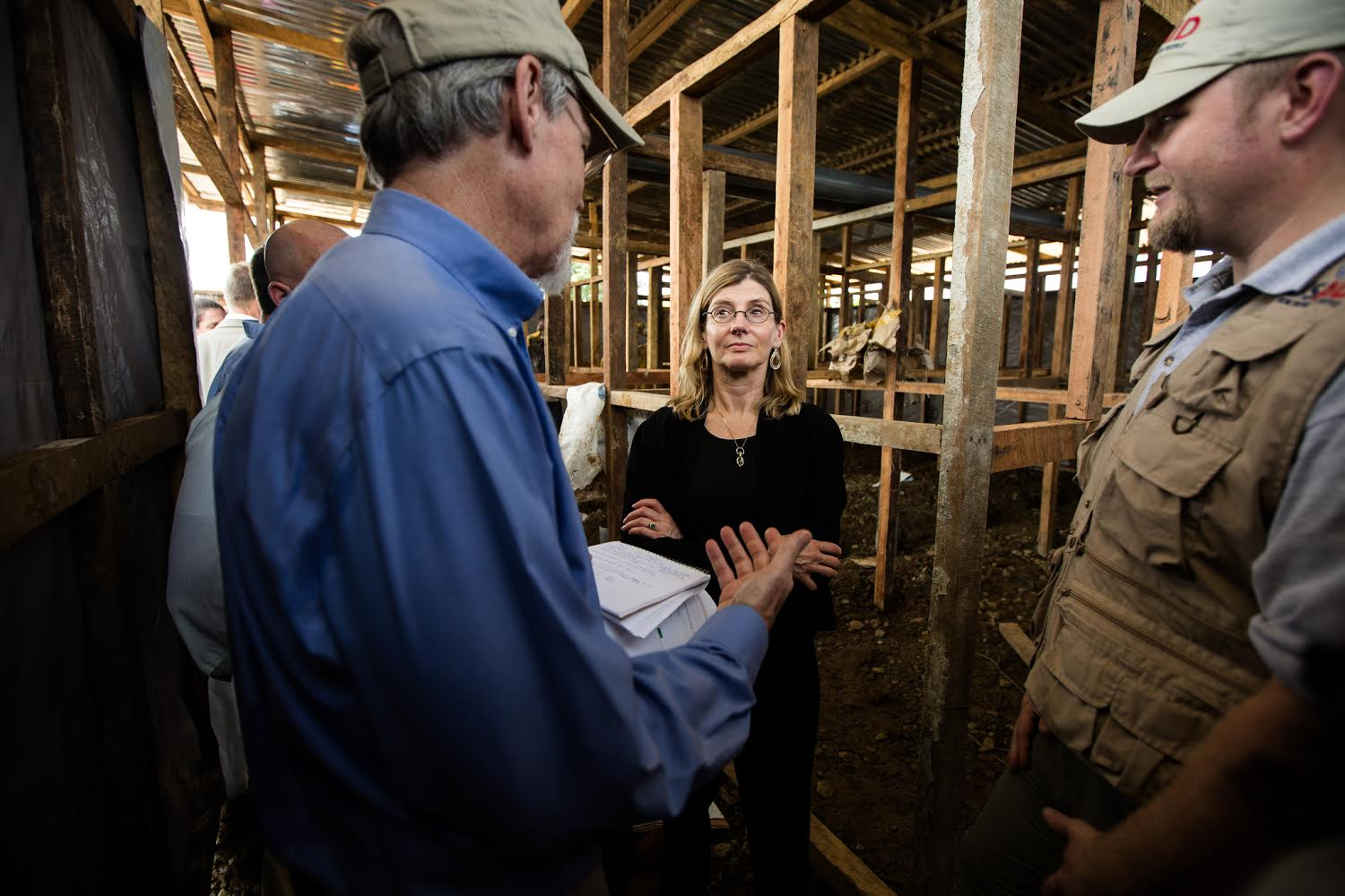 Bill Berger, who leads a USAID disaster assistance response team, briefs administrator Nancy Lindborg at an Ebola treatment unit construction site in Monrovia, Liberia, Oct. 1, 2014.