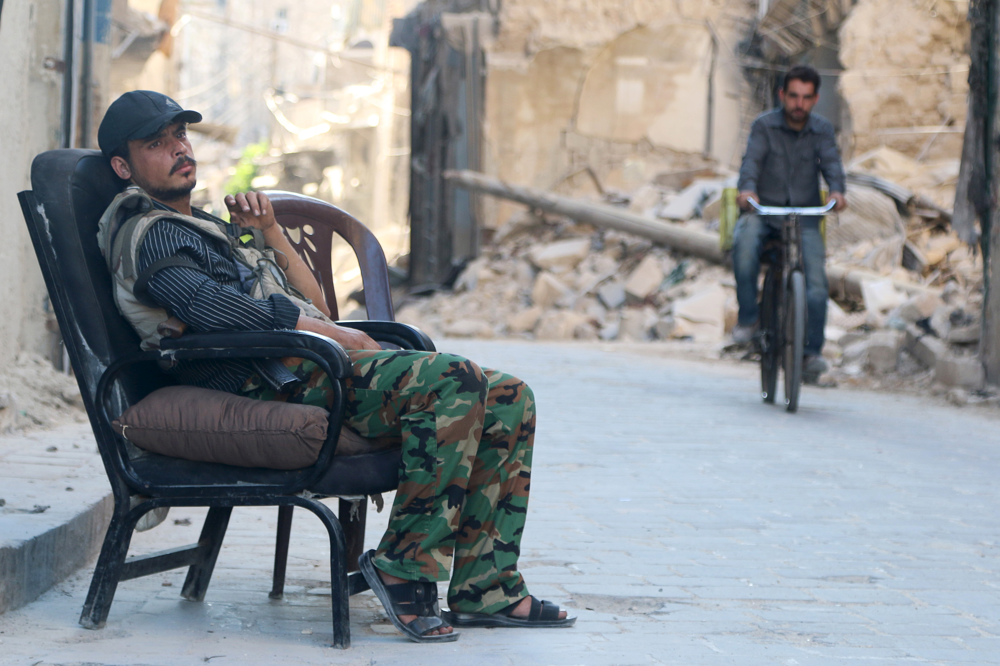 FILE - A Free Syrian Army fighter sits at a checkpoint as a man rides a bicycle past the rubble of a damaged building in the old city of Aleppo, Syria, July 13, 2015.