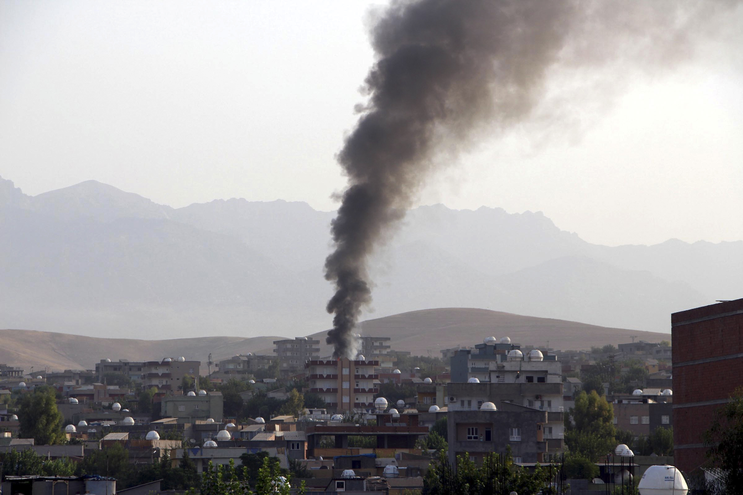 Smoke billows from a fire during firefight between the police and Kurdistan Workers' Party, or PKK militants in the town of Silopi, southeastern Turkey, July 7, 2015.