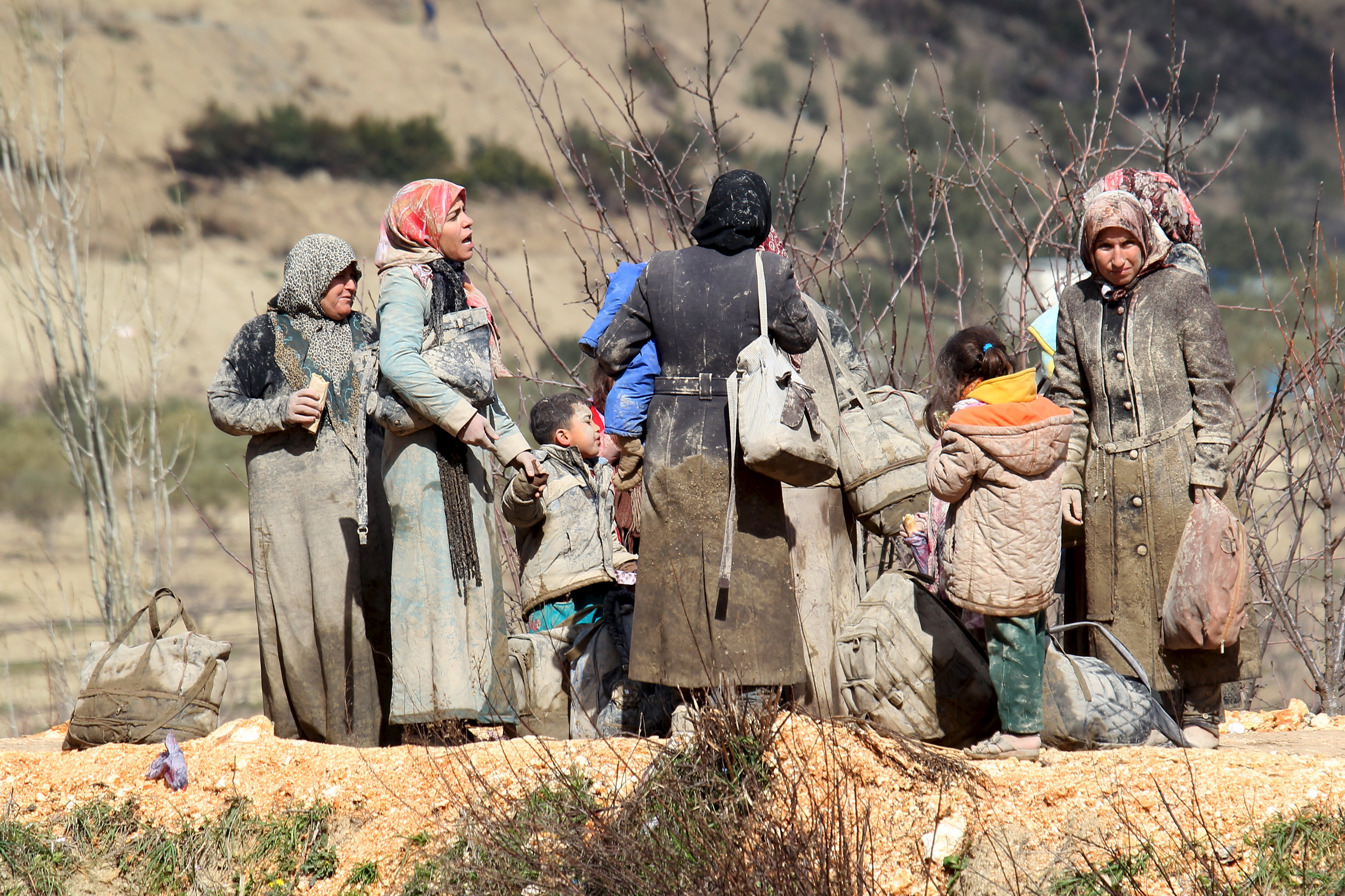 Internally displaced people, covered with mud, wait as they are stuck in the town of Khirbet Al-Joz, in Latakia countryside, waiting to get permission to cross into Turkey near the Syrian-Turkish border, Syria, Feb. 7, 2016.