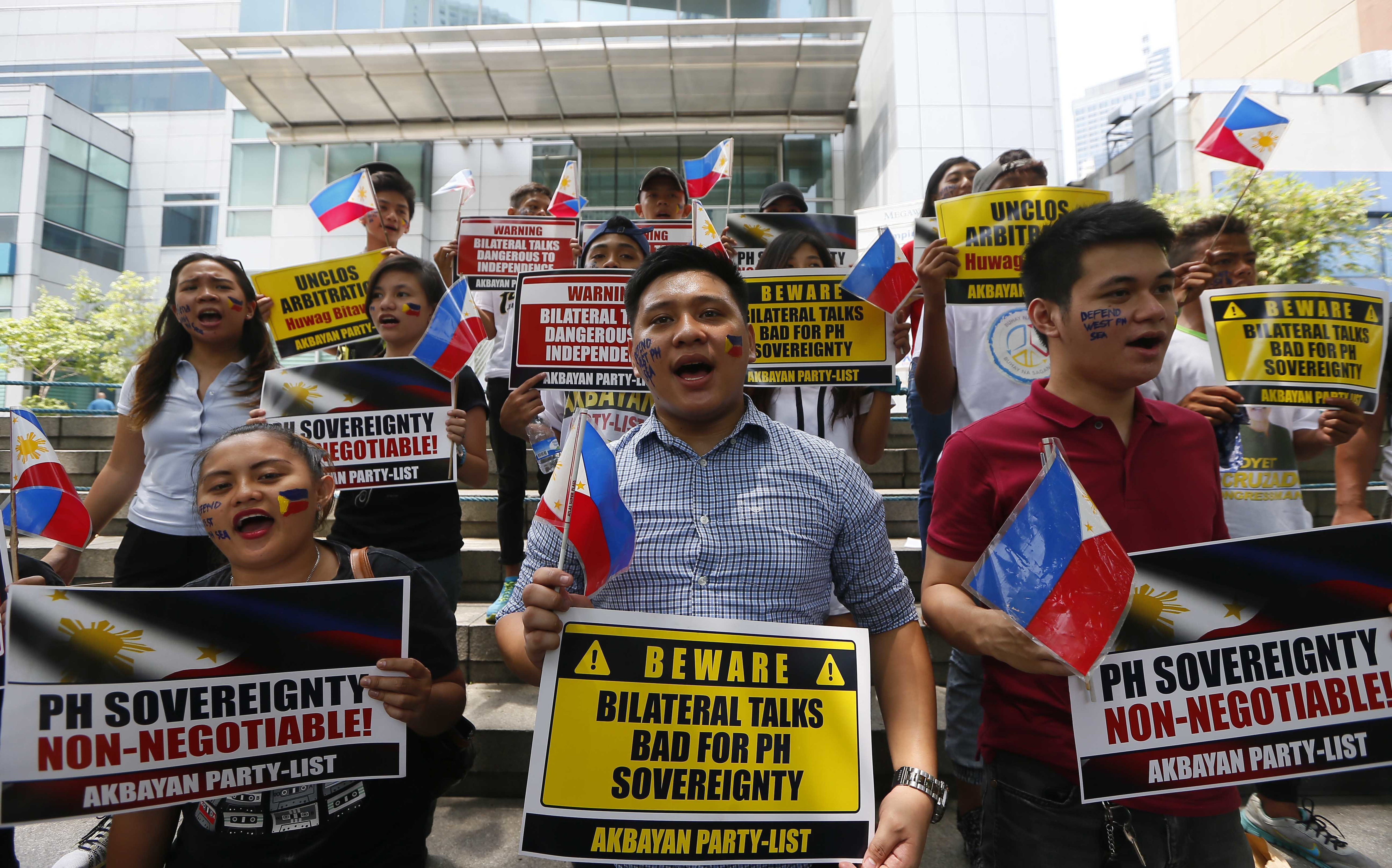 FILE - Protesters shout slogans and display placards outside of the Chinese Consulate in protest of China's occupation and island-building in the disputed Spratly Island group in the South China Sea in Makati city's financial district east of Manila,...