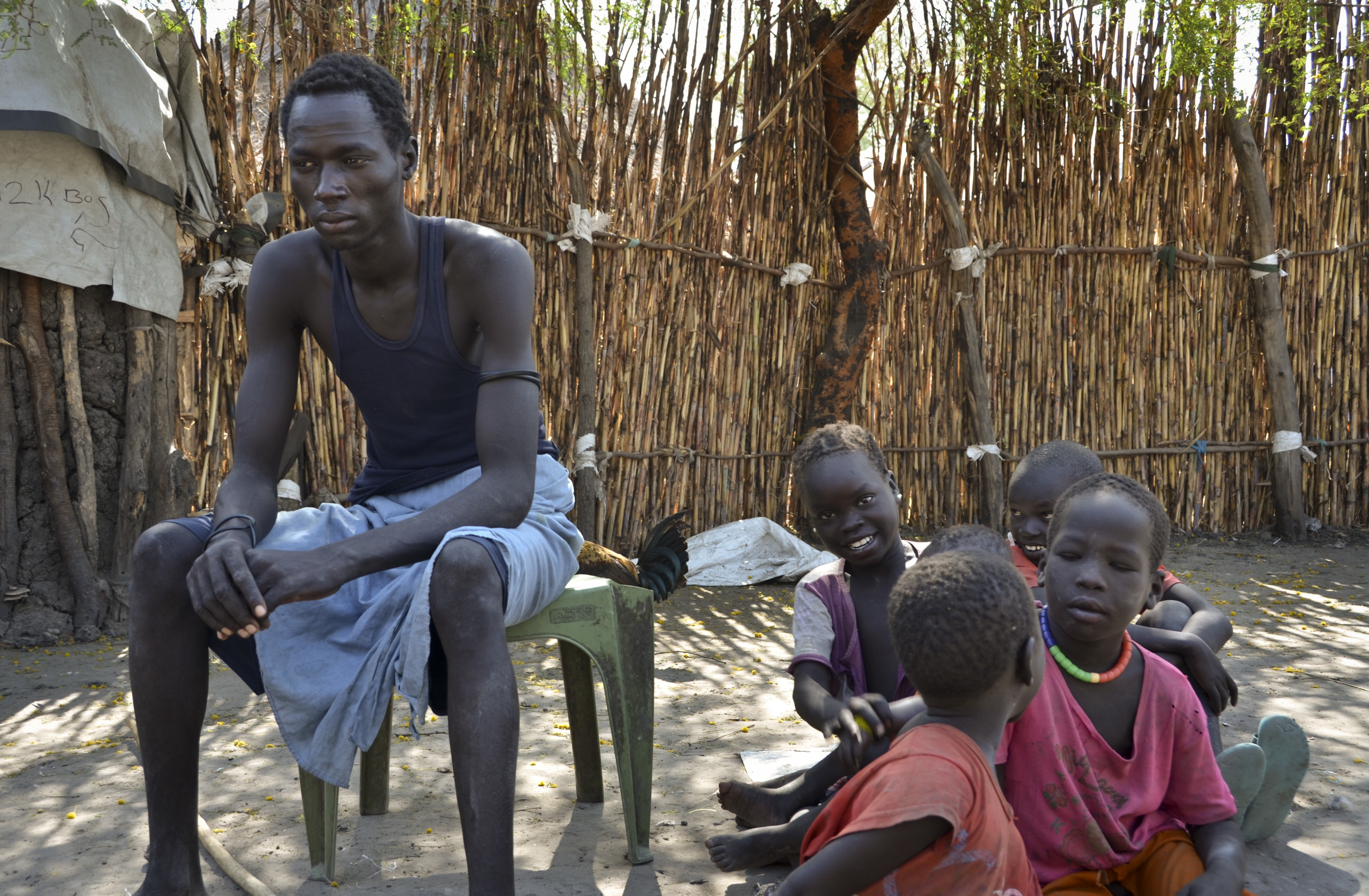 FILE - A South Sudanese man, who says he was shot in the back and thigh by government soldiers while trying to get food in a nearby town in order to feed his starving family, sits with his five children outside his house in Jiech, Ayod County, South ...
