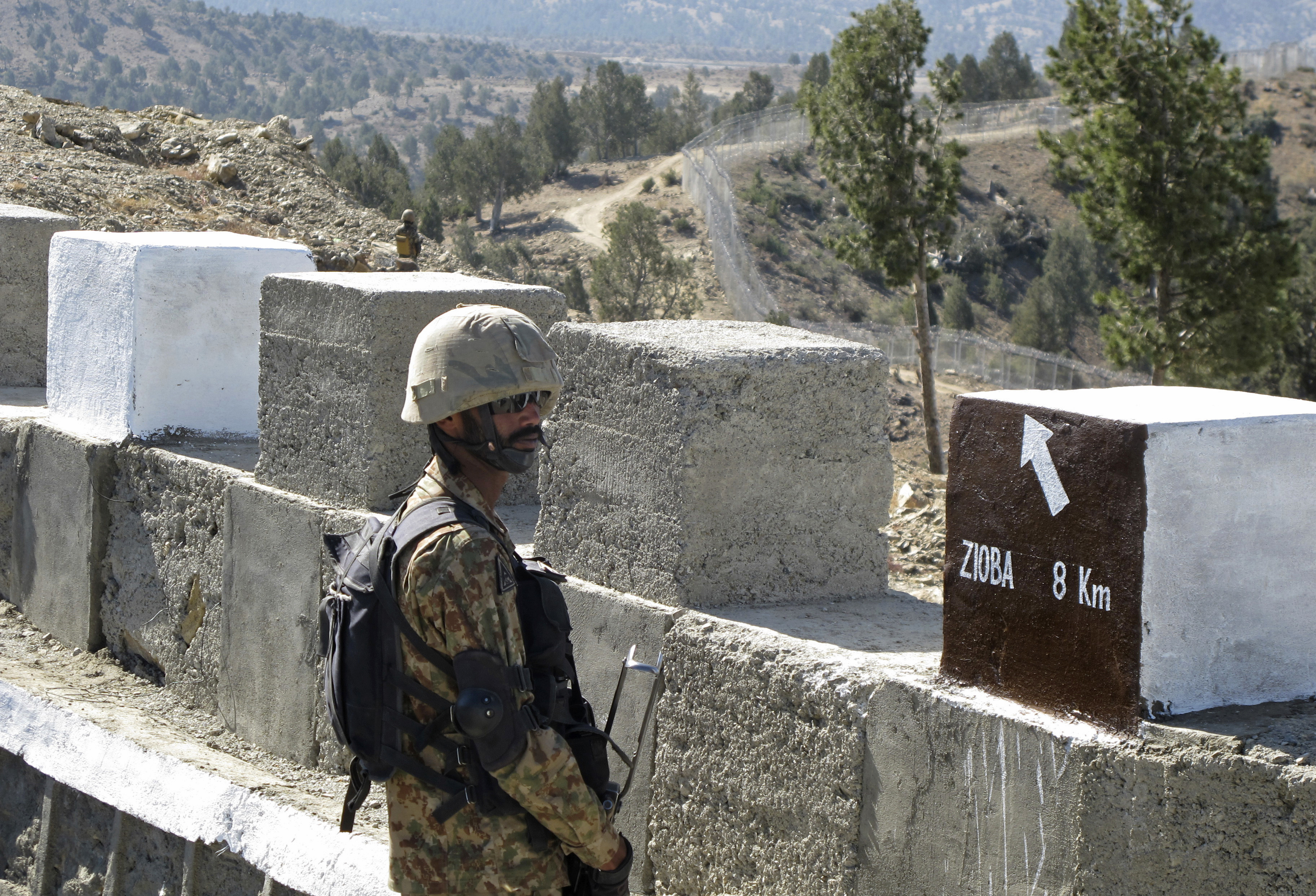 A Pakistani soldier stands guard at a newly erected fence between Pakistan and Afghanistan at Angore Adda, Pakistan, Oct. 18, 2017.