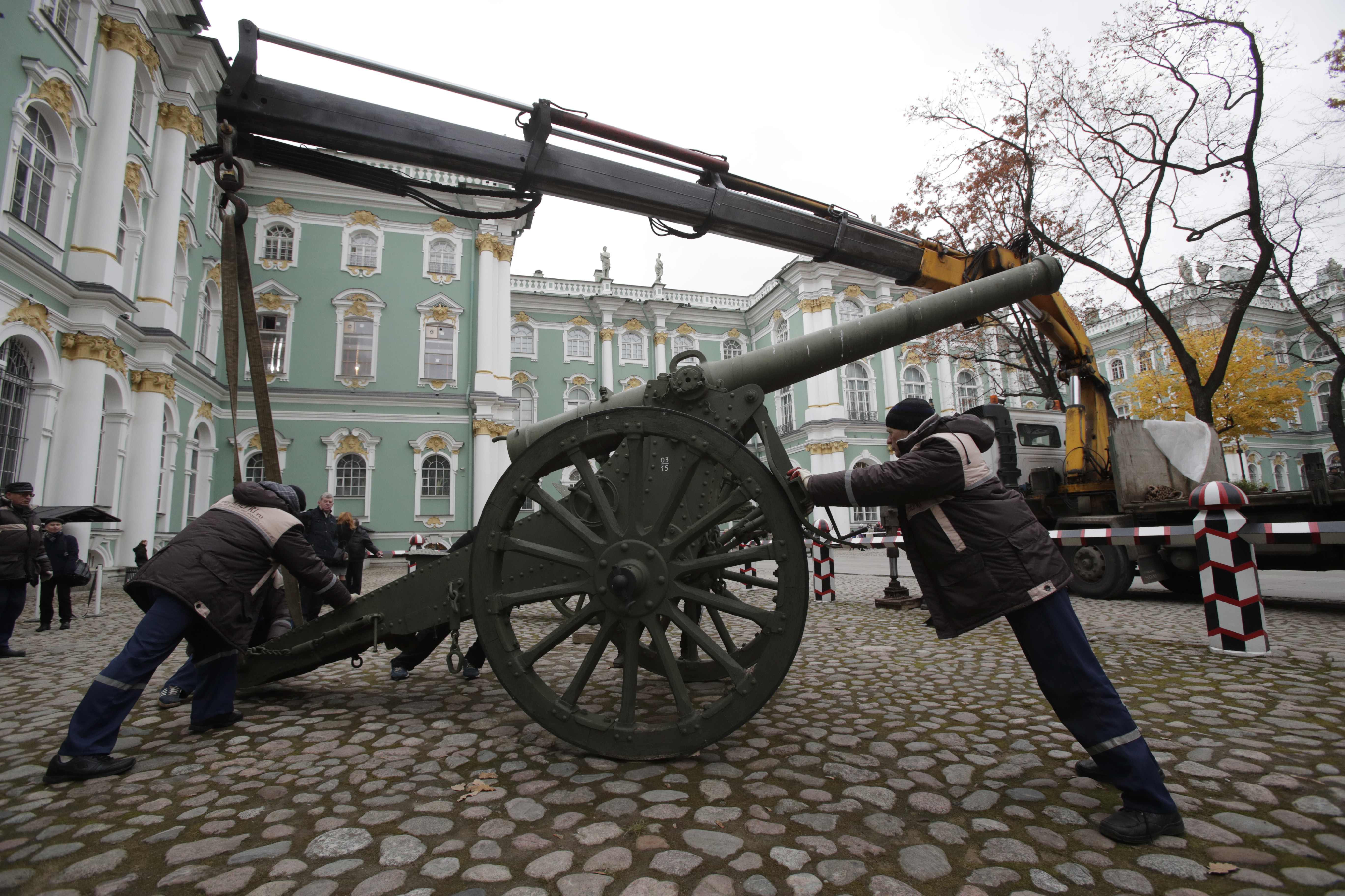 Workers install a gun in the yard of the Winter Palace in the State Hermitage Museum in St.Petersburg, Russia, Oct. 24, 2017, as part of preparations for an exhibition marking the centenary of the October Revolution.