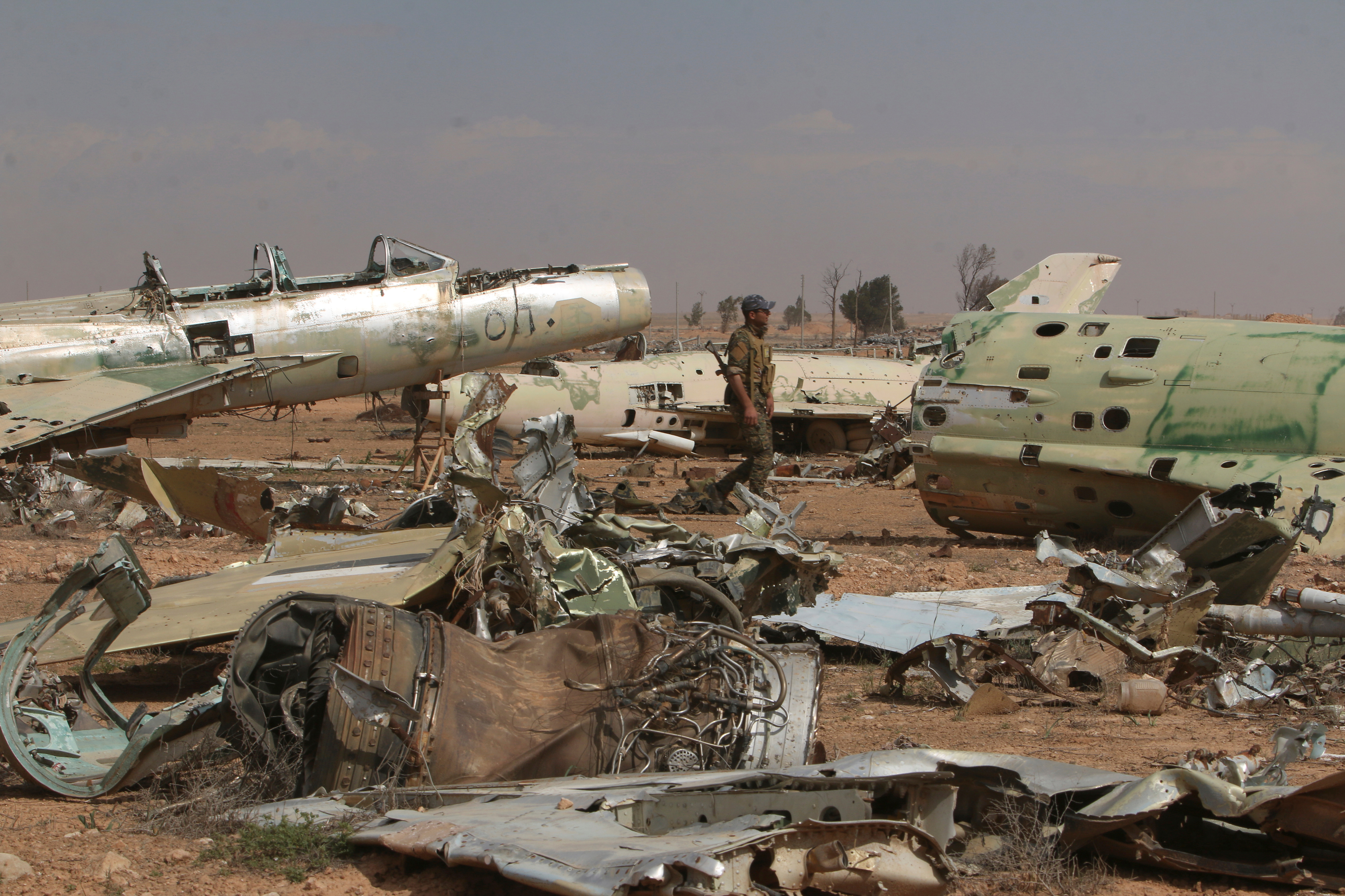 A Syrian Democratic Forces (SDF) fighter walks near destroyed airplane parts inside Tabqa military airport after taking control of it from Islamic State fighters, west of Raqqa city, Syria April 9, 2017.