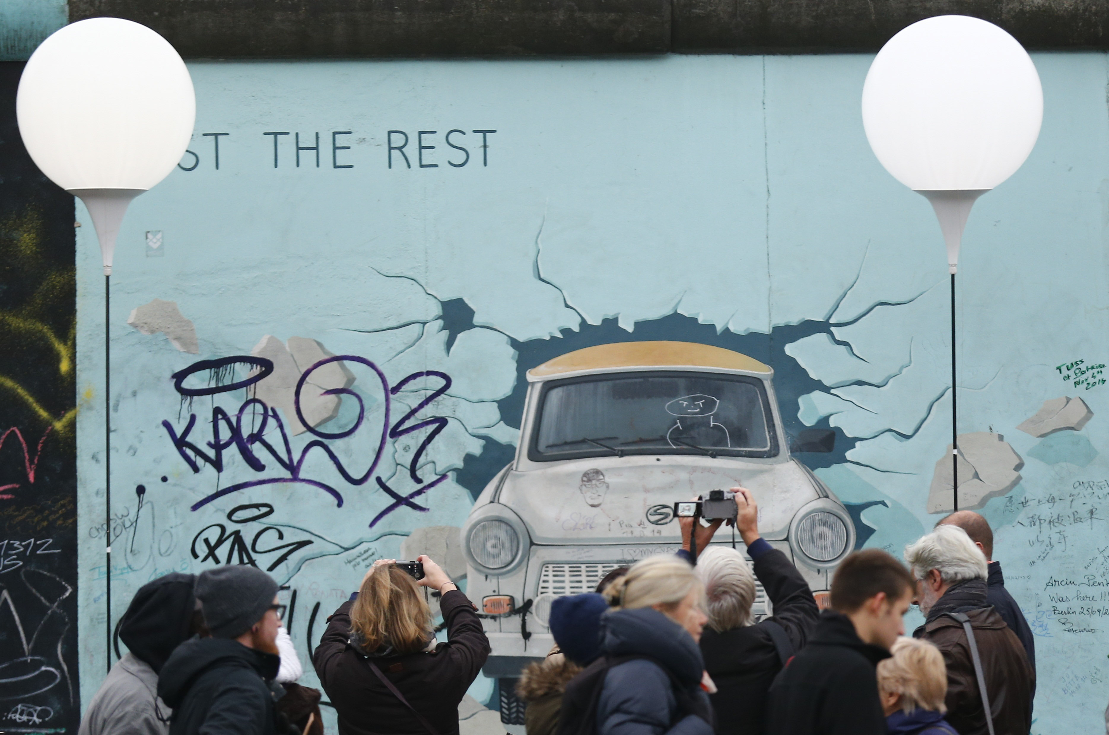 People stroll past and take pictures next to the installation 'Lichtgrenze' (Border of Light) along the East Side Gallery, the largest remaining part of the former Berlin Wall, Berlin, Germany, Nov. 9, 2014.