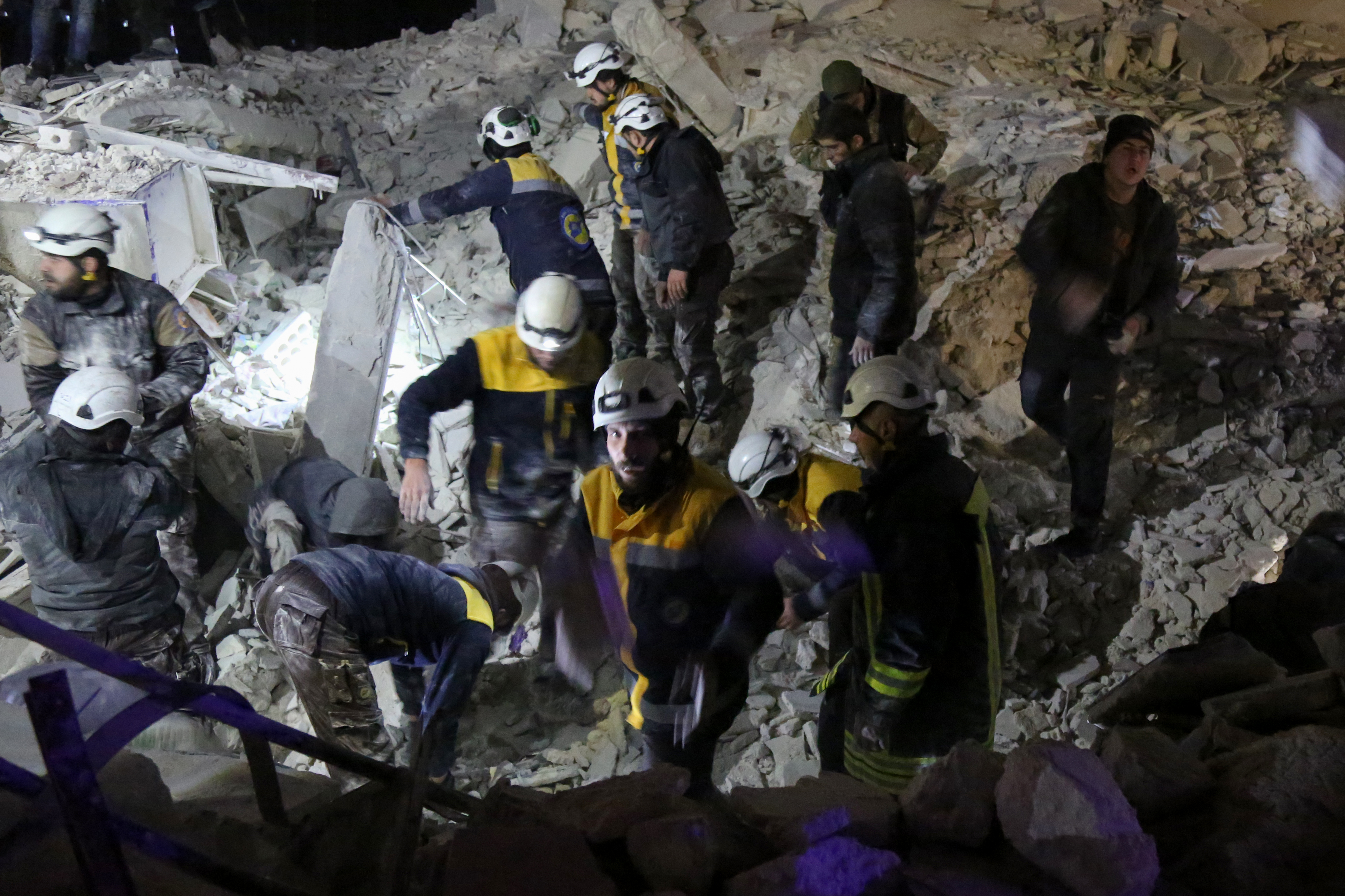 Syrian emergency personnel search for victims following an explosion at a base for Asian jihadists in a rebel-held area of the northwestern city of Idlib, Jan. 7, 2018.
