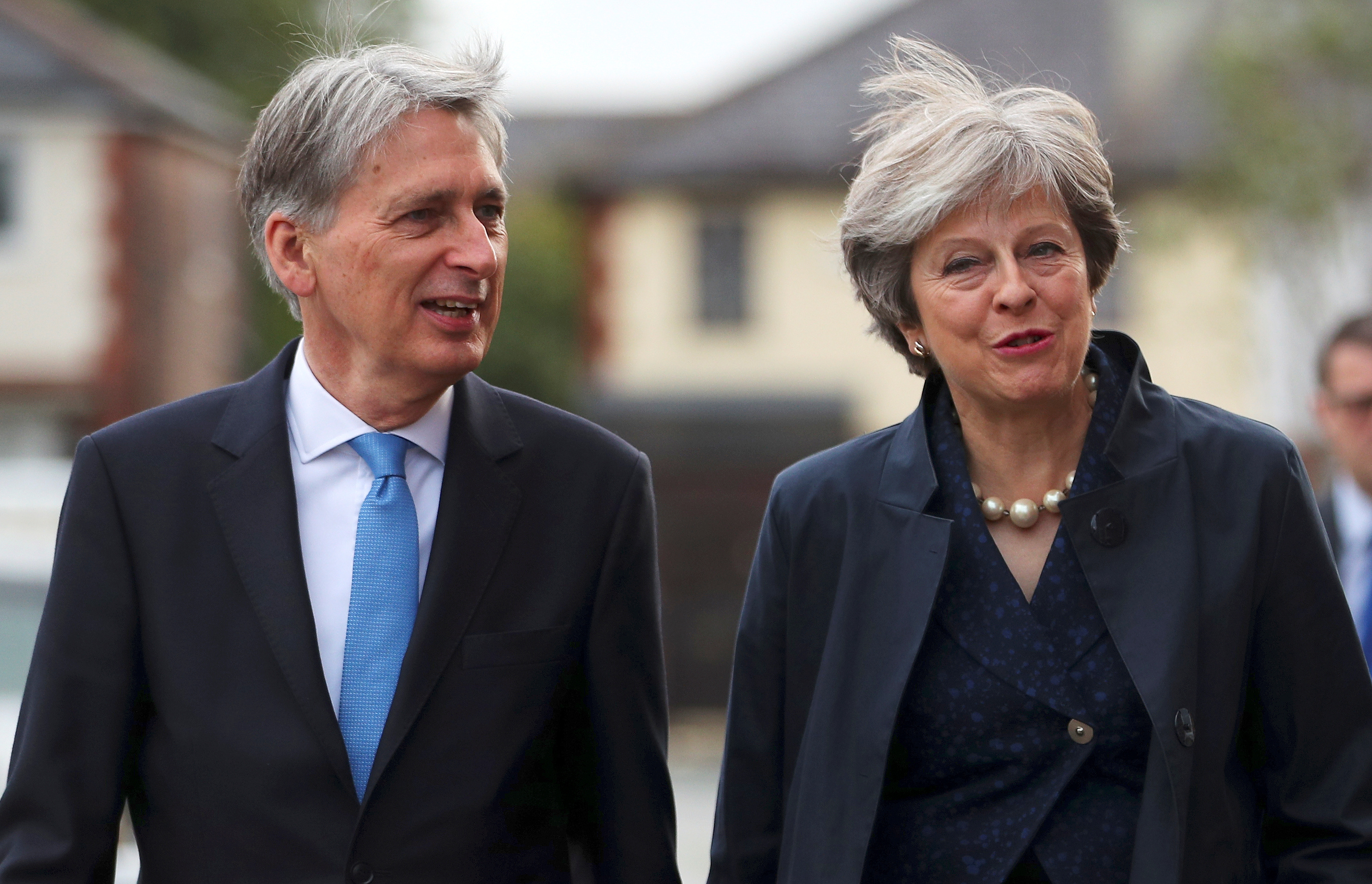 Britain's Prime Minister Theresa May and Chancellor of the Exchequer Philip Hammond visit a home near the Conservative Party's conference in Manchester, Oct. 2, 2017.