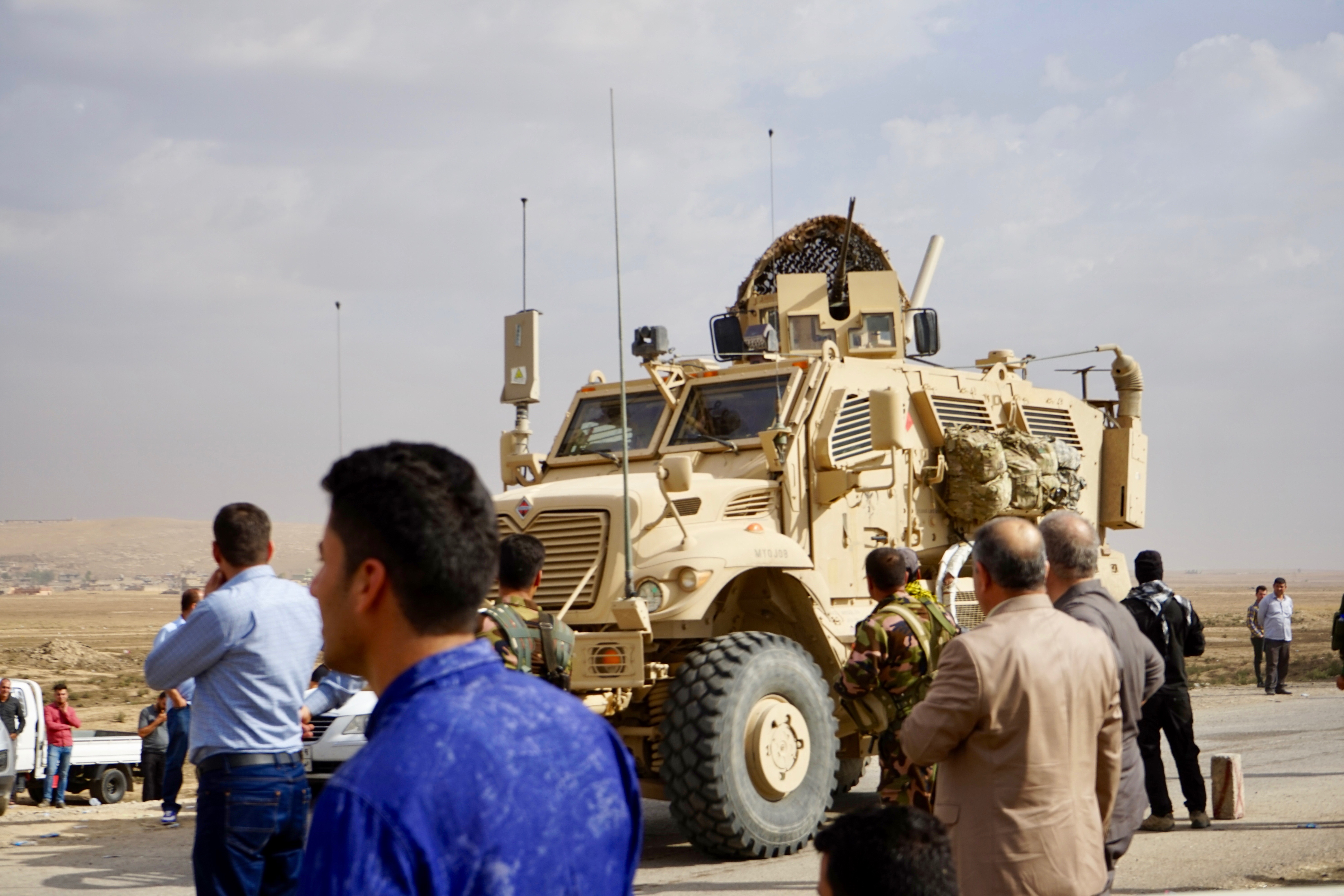 Iraqi Christians on the outskirts of the town of Bartilla watch Iraqi military vehicles advancing. Most Christians have been blocked from visiting their homes with Iraqi military officials saying the area remains unsafe, Bartilla, Iraq, Oct. 31, 2016...