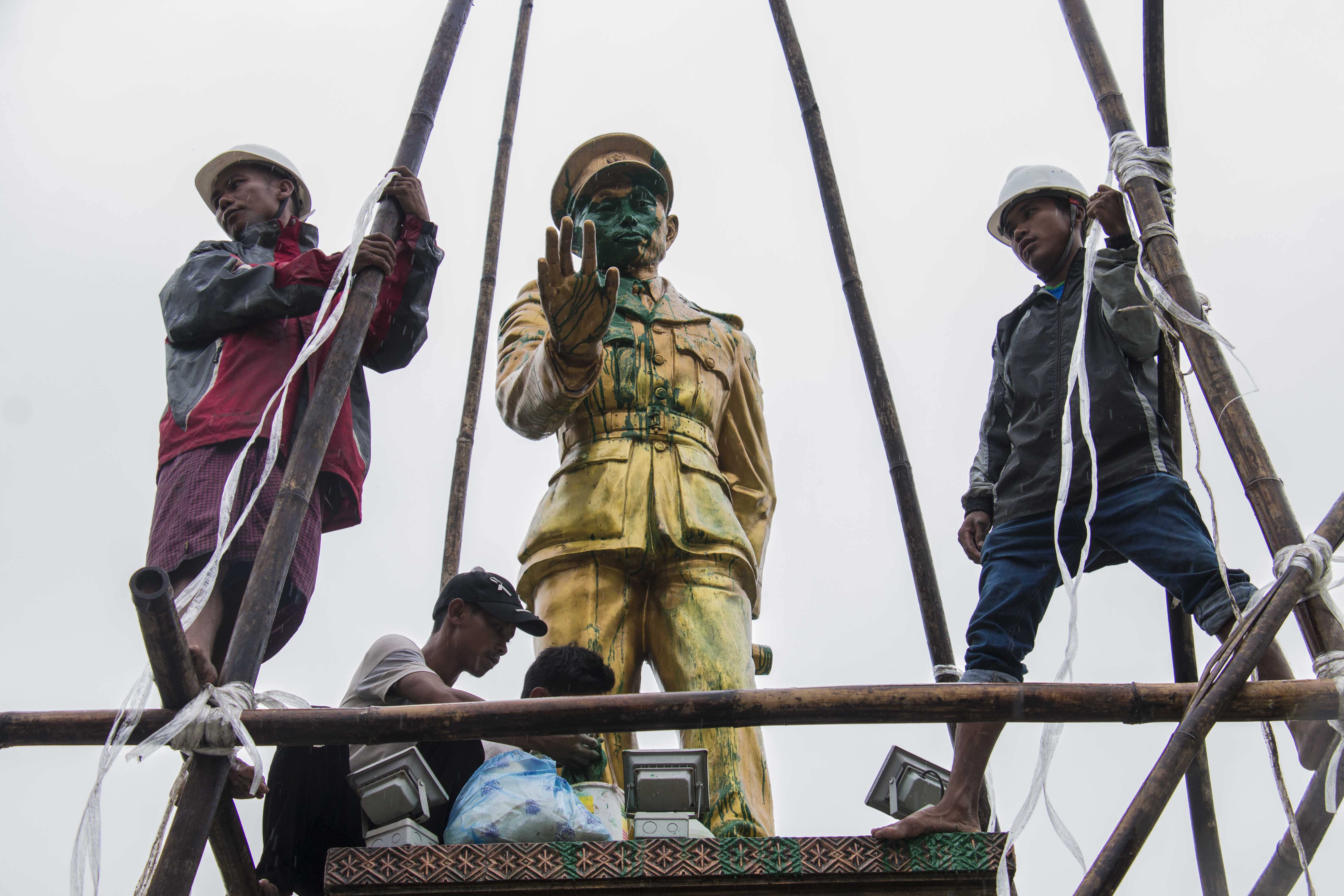 FILE - workers clean a vandalized statue of Myanmar independence hero Gen. Aung San, in Myitkyina, capital of Kachin state, Myanmar, July 23, 2018.
