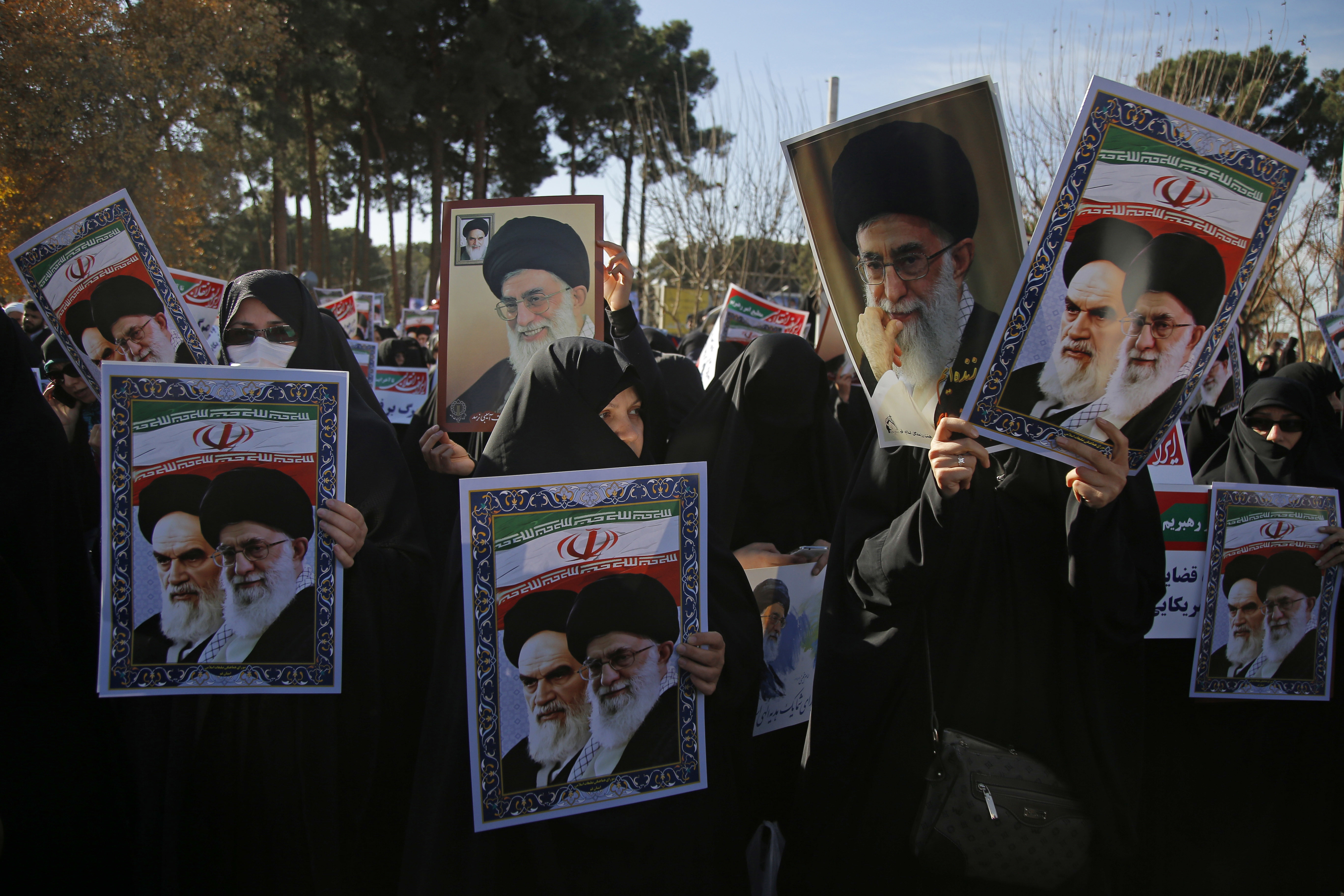 In this photo provided by Tasnim News Agency, women hold posters showing portraits of late Iranian revolutionary founder Ayatollah Khomeini, and Supreme Leader Ayatollah Ali Khamenei during a pro-government rally in the holy city of Qom, Iran, Jan. 3...