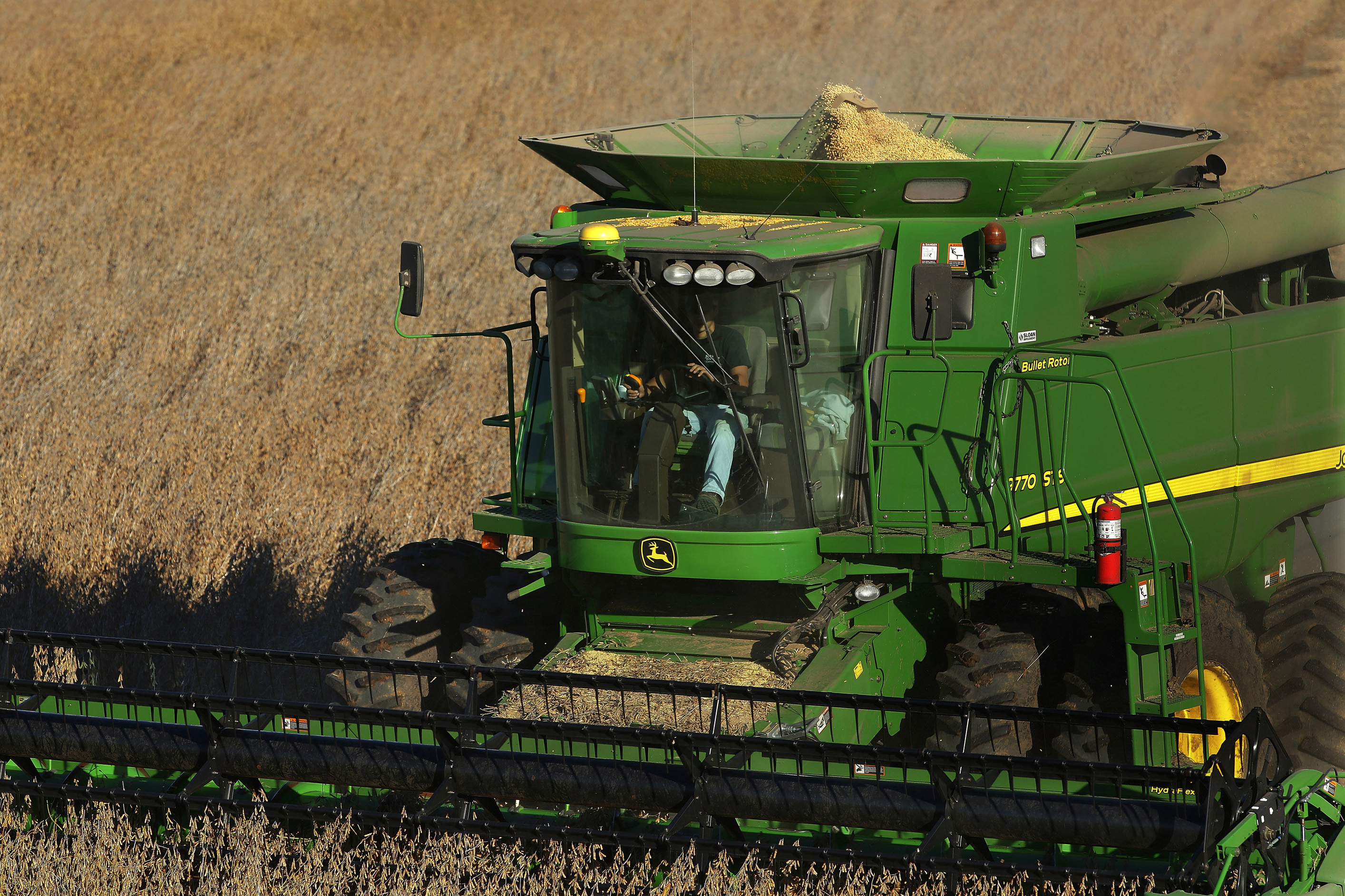 FILE - A farmer uses a combine to harvest his soybean field Oct. 21, 2014, in Loami, Ill.