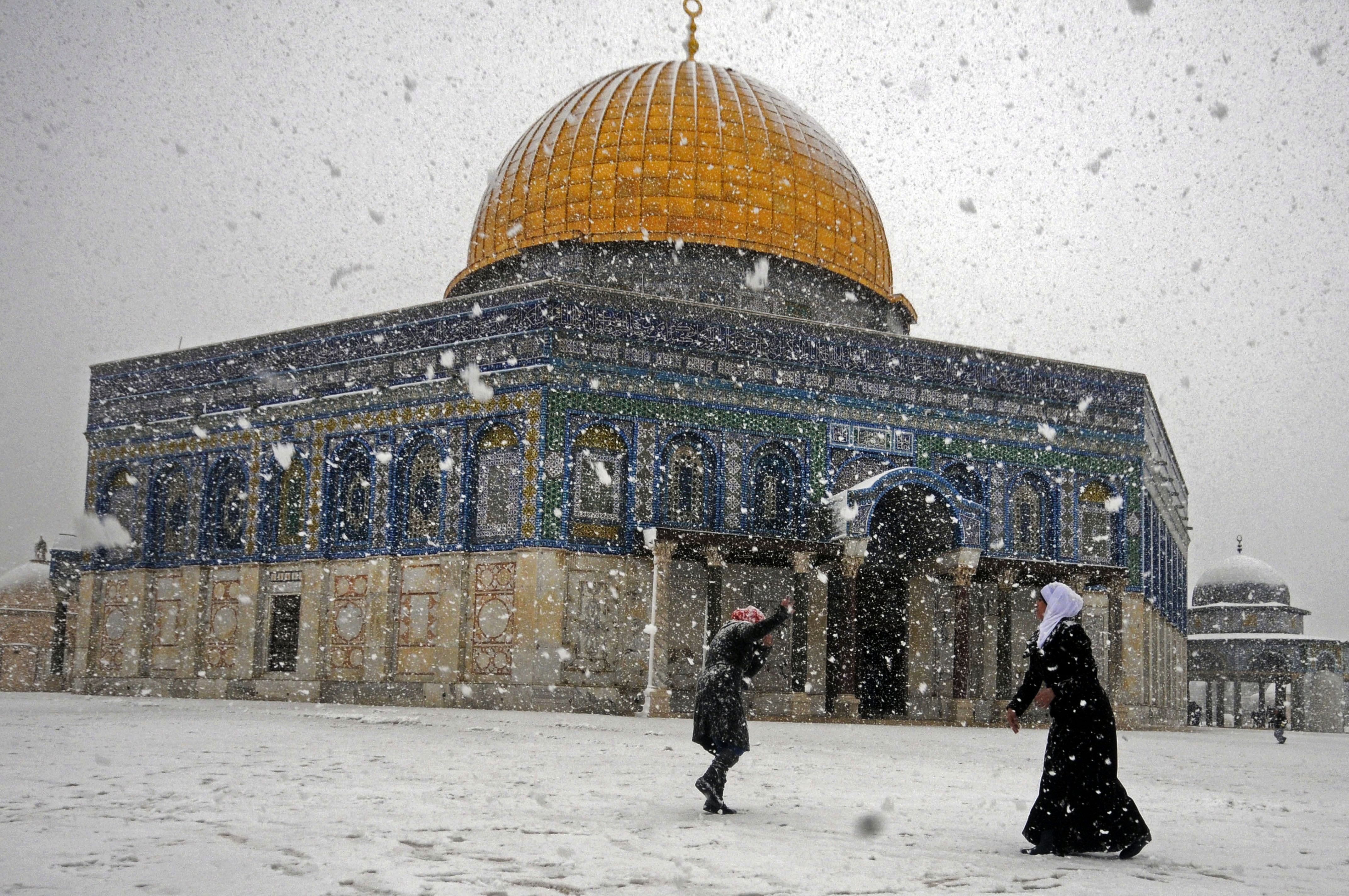 Two Palestinian women play with snow outside Al-Aqsa Mosque in Jerusalem, Dec. 12, 2013.