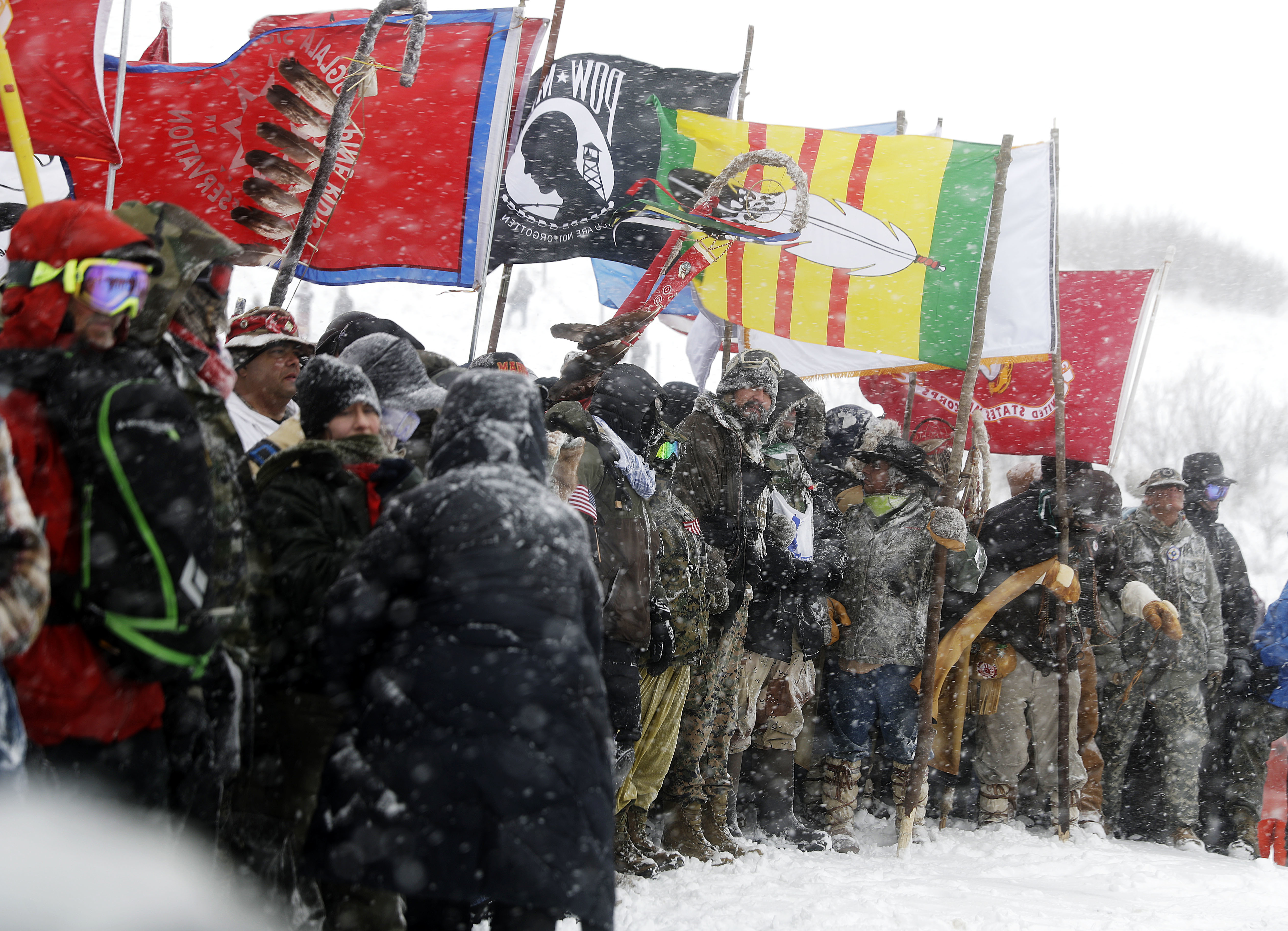 FILE - In this Dec. 5, 2016, file photo, military veterans and Native American tribal elders come to a stop for a ceremonial prayer during a march to a closed bridge across from the Dakota Access oil pipeline site in Cannon Ball, N.D.