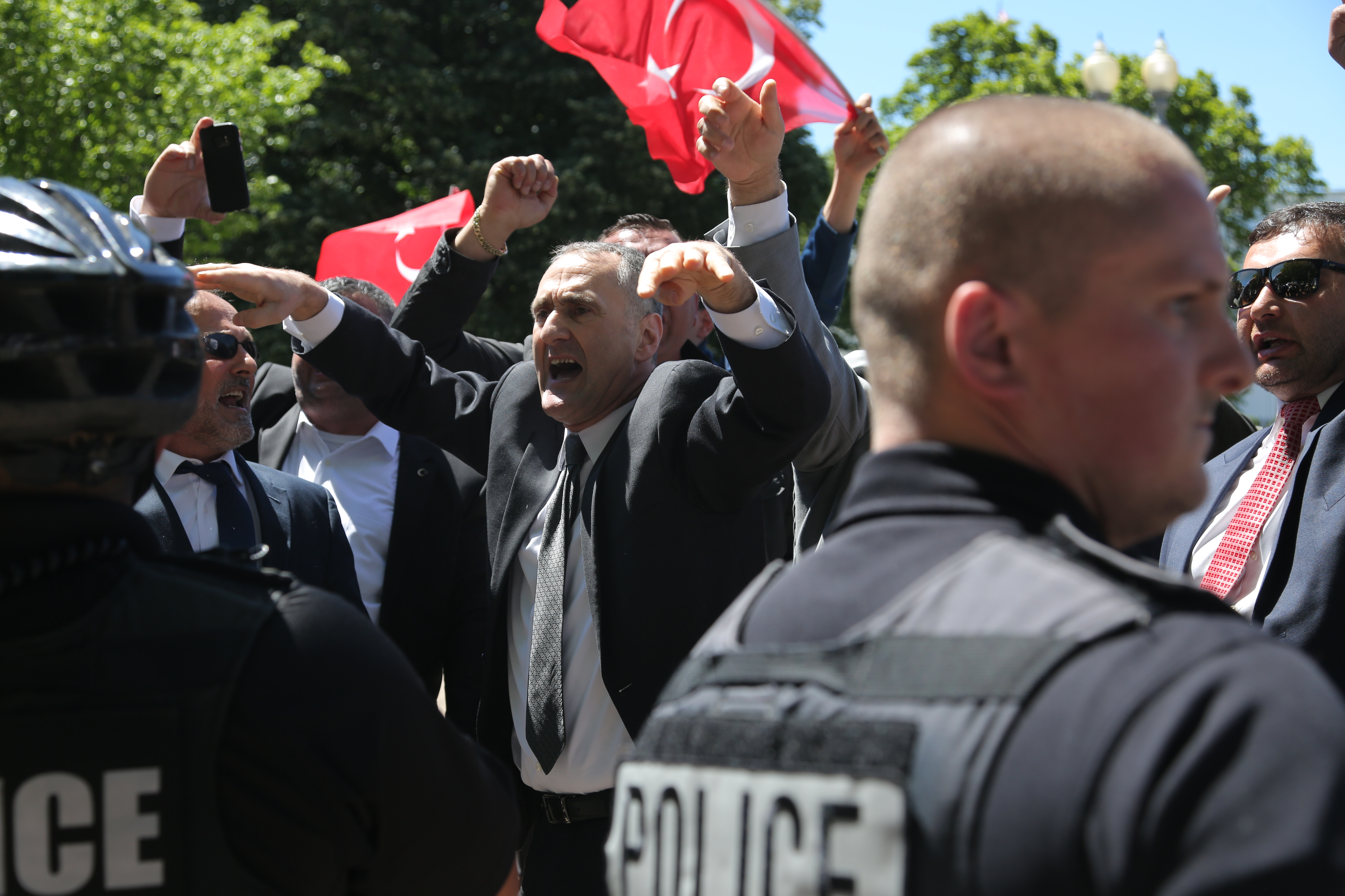 Supporters of Turkish President Recep Tayyip Erdogan react to anti-Erdogan supporters on the other side of a line of police officers outside the White House in Washington, D.C., May 16, 2017.