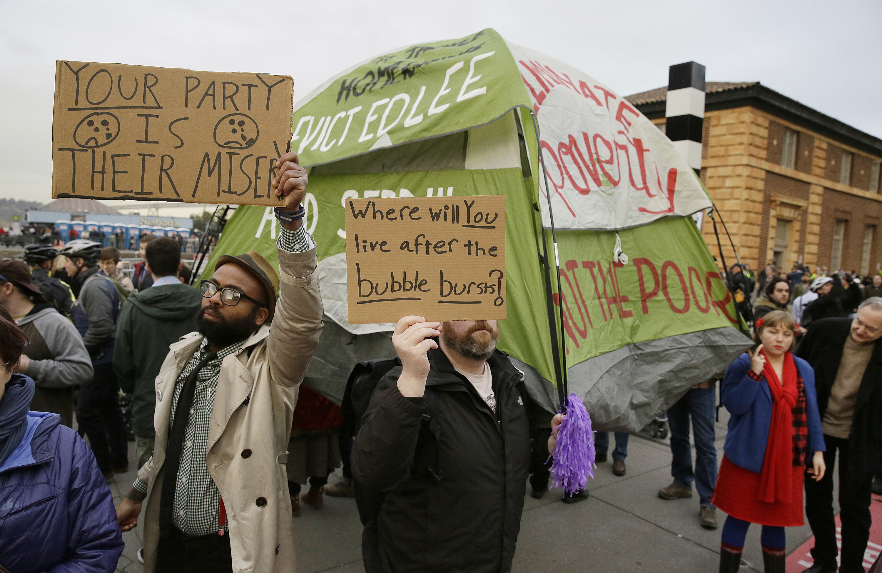 FILE - People hold up signs and a tent during a protest to demand city officials do more to help homeless people in San Francisco, California, Feb. 3, 2016.