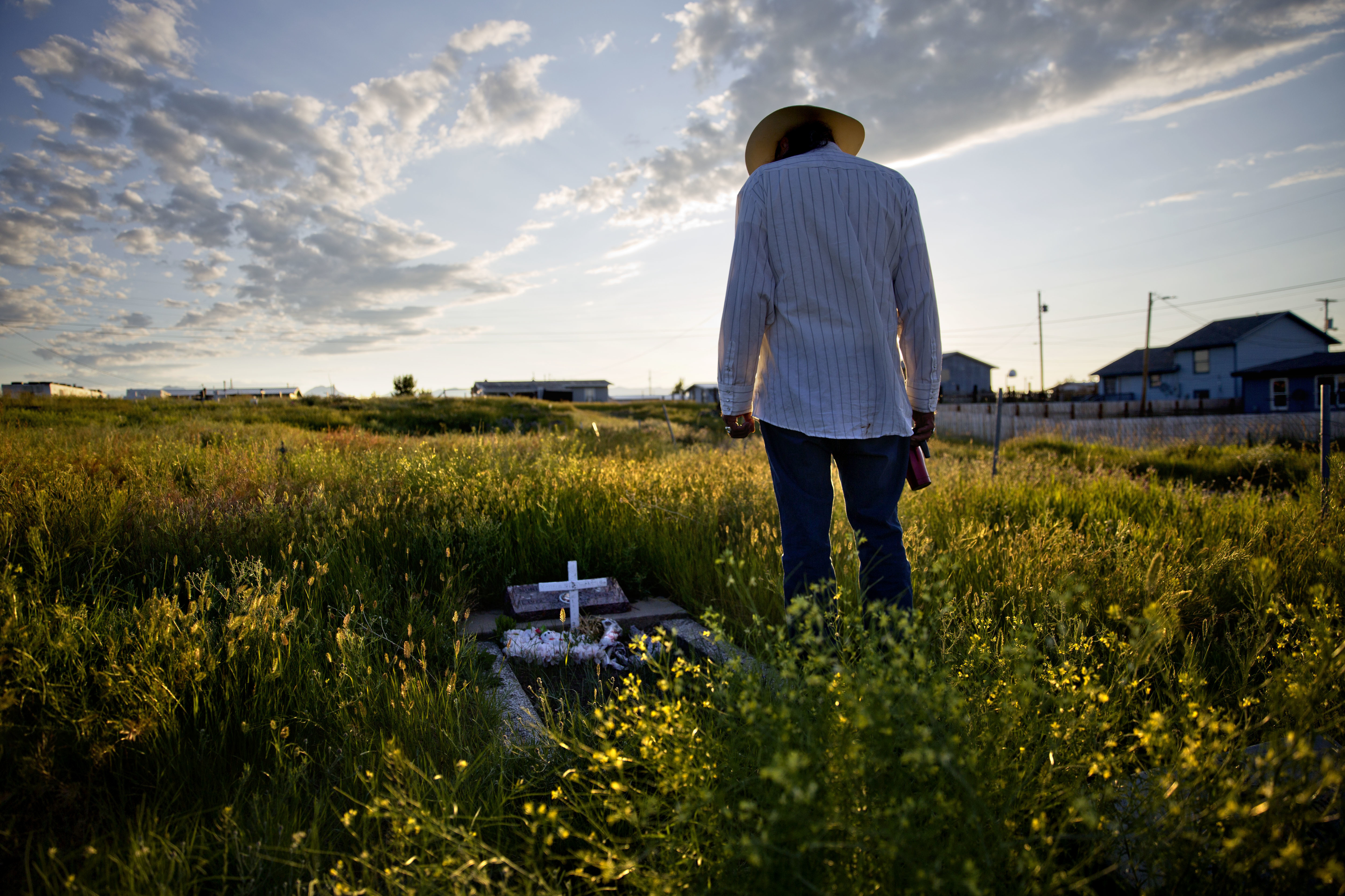 """Kenny Still Smoking stands over the tombstone of his 7-year-old daughter, Monica, who disappeared from school in 1979 and was found frozen on a mountain, as he visits her grave on the Blackfeet Indian Reservation in Browning, Mont., July 14, 2018. """"I..."""