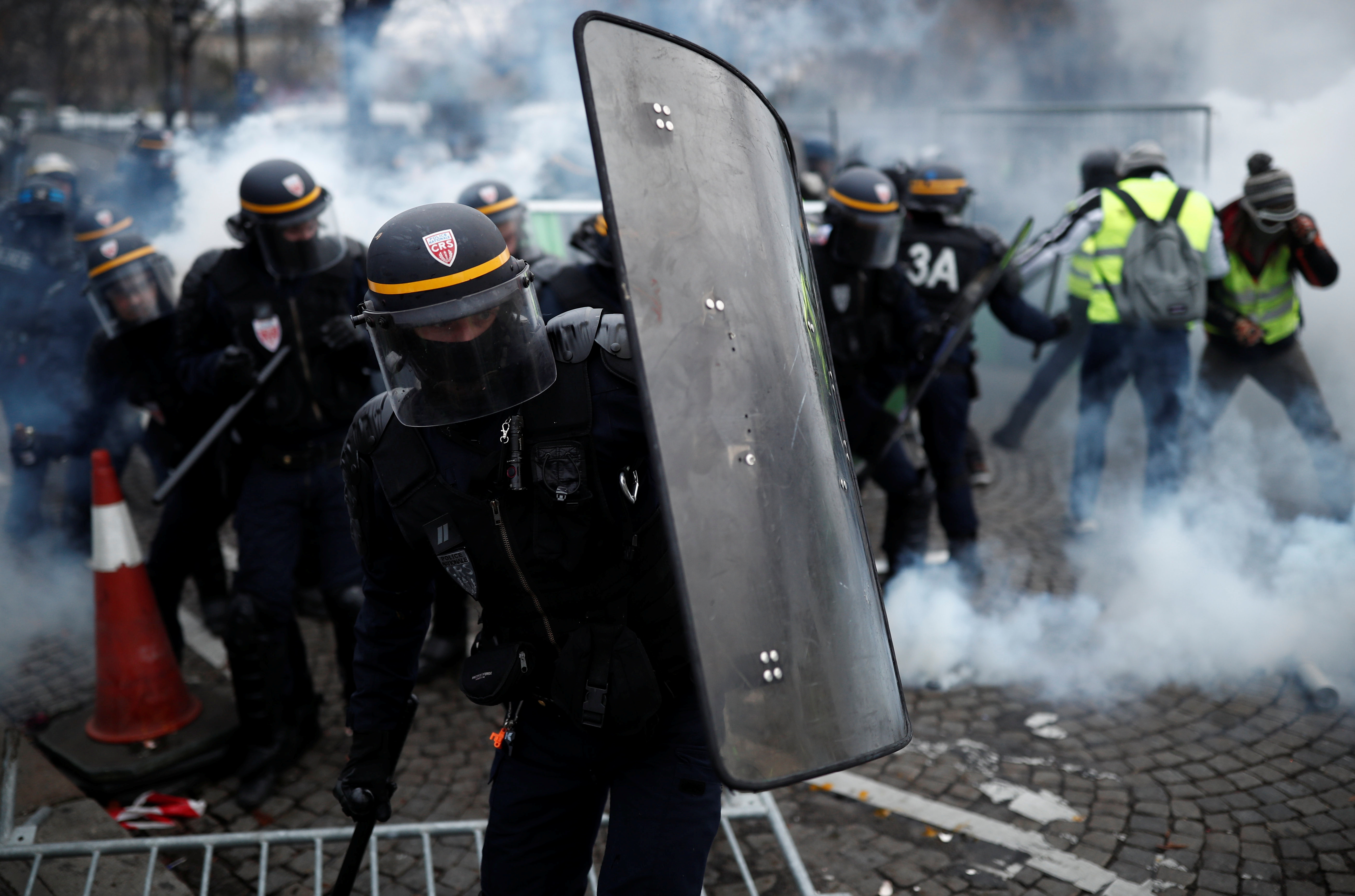 Protesters wearing yellow vests, a symbol of a French drivers' protest against higher fuel prices, clash with riot police on the Champs-Elysee in Paris, Nov. 24, 2018.