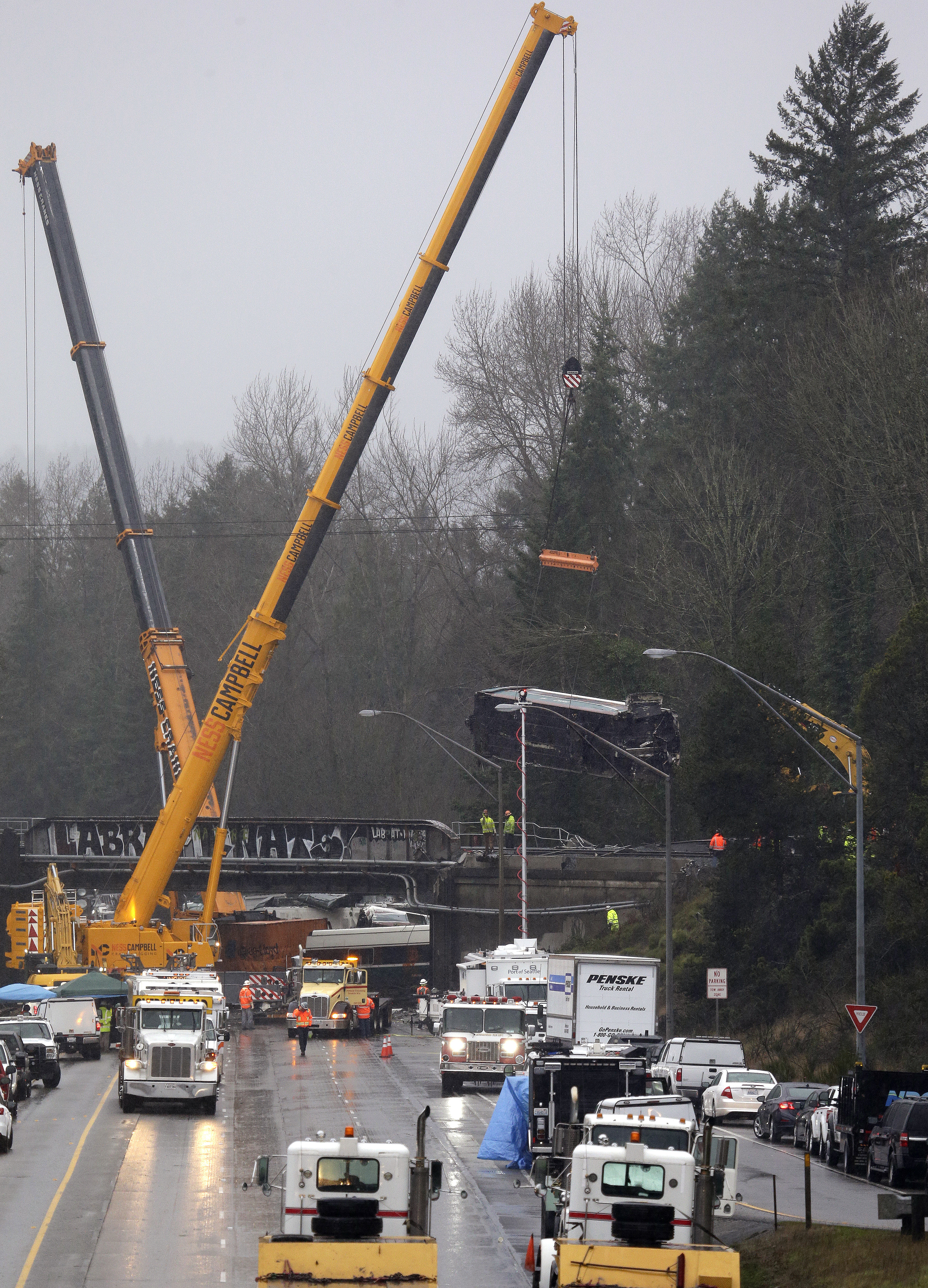 A crane is used to lower a damaged Amtrak train car from an overpass at the scene of Monday's deadly train crash onto Interstate 5 in DuPont, Washington, Dec. 19, 2017.