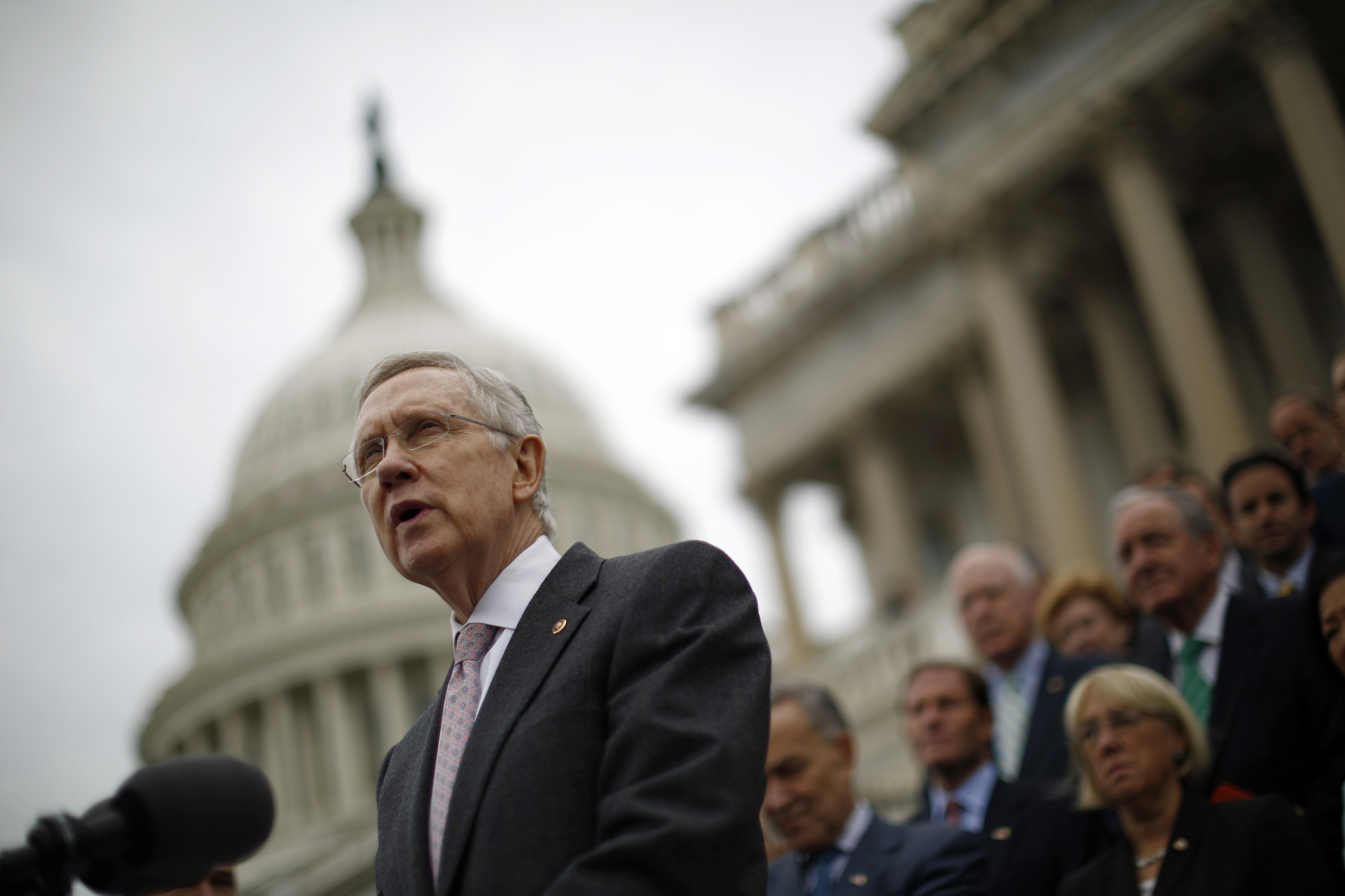 FILE - U.S. Senate Majority Leader Harry Reid, with other Democratic Party Senate members in the background, is seen on the steps of the U.S. Capitol in Washington, D.C.