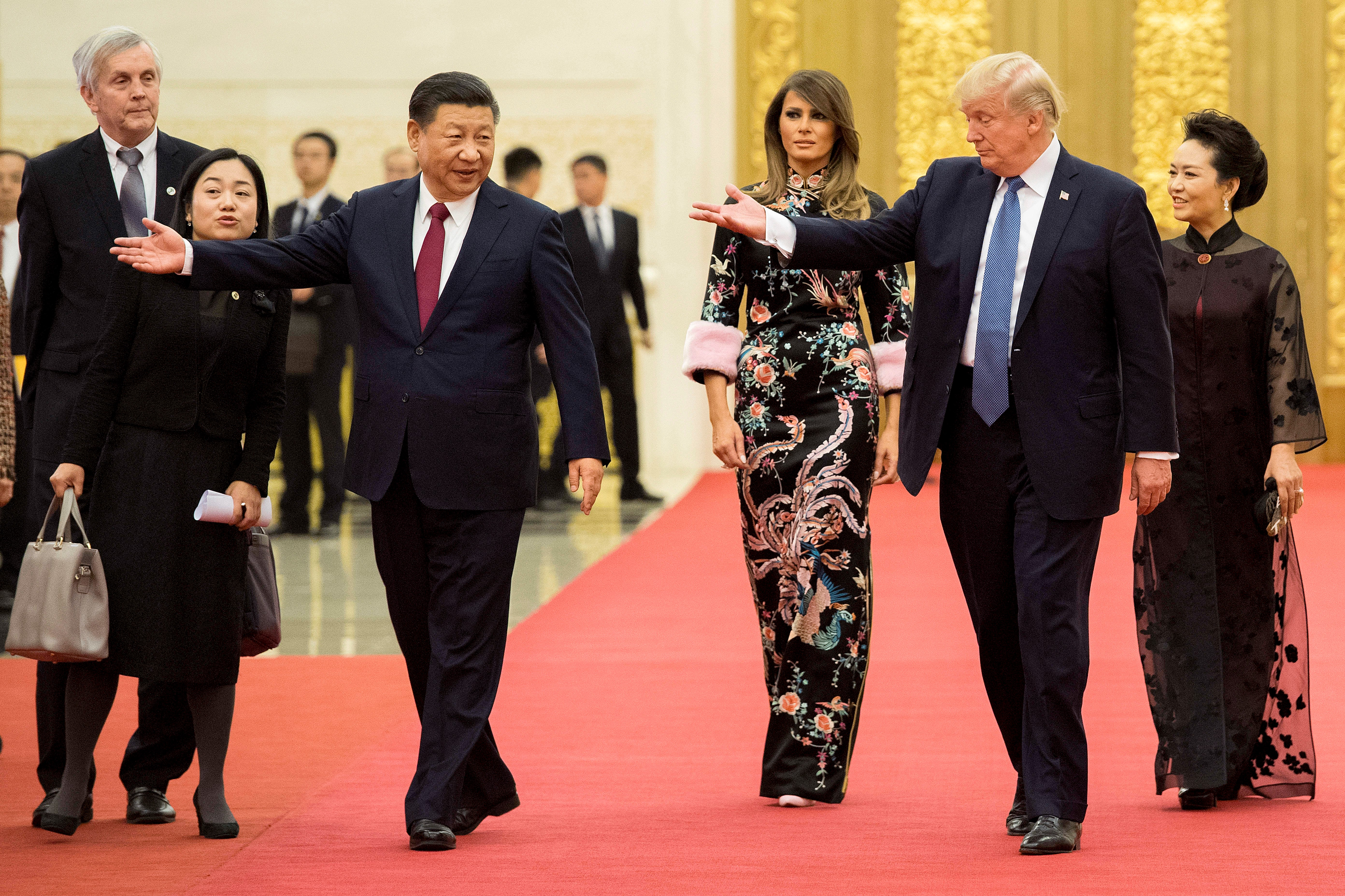 U.S. President Donald Trump, second right, gestures toward China's President Xi Jinping, third left, as U.S. first lady Melania Trump, center, and Xi's wife Peng Liyuan, right, look on at the Great Hall of the People in Beijing, Nov. 9, 2017.