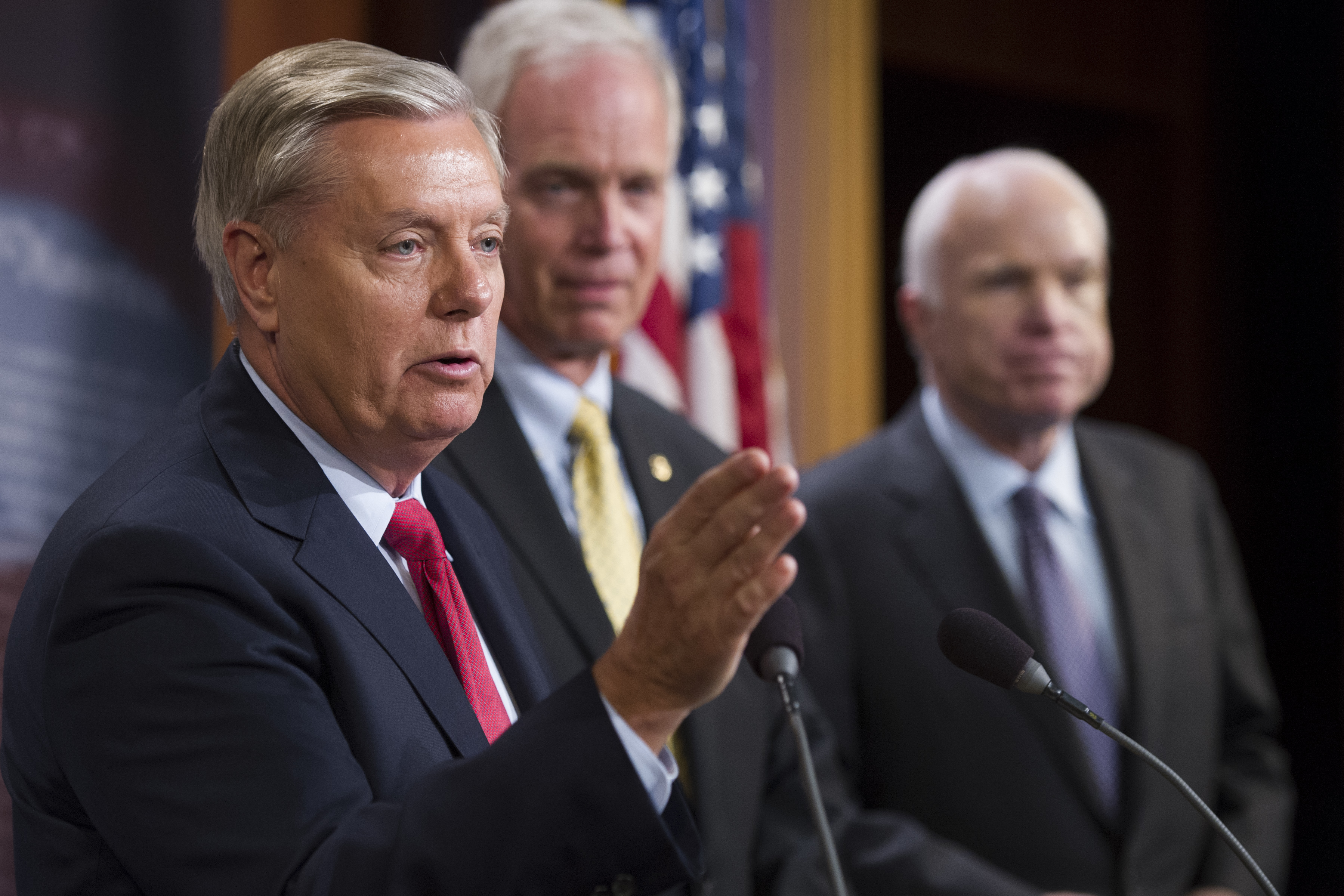 From left, Sen. Lindsey Graham, R-S.C., Sen. Ron Johnson, R-Wis., and Sen. John McCain, R-Ariz., speak to reporters at the Capitol. McCain joined two other Republican senators to defeat a measure to partly repeal the Affordable Care Act.