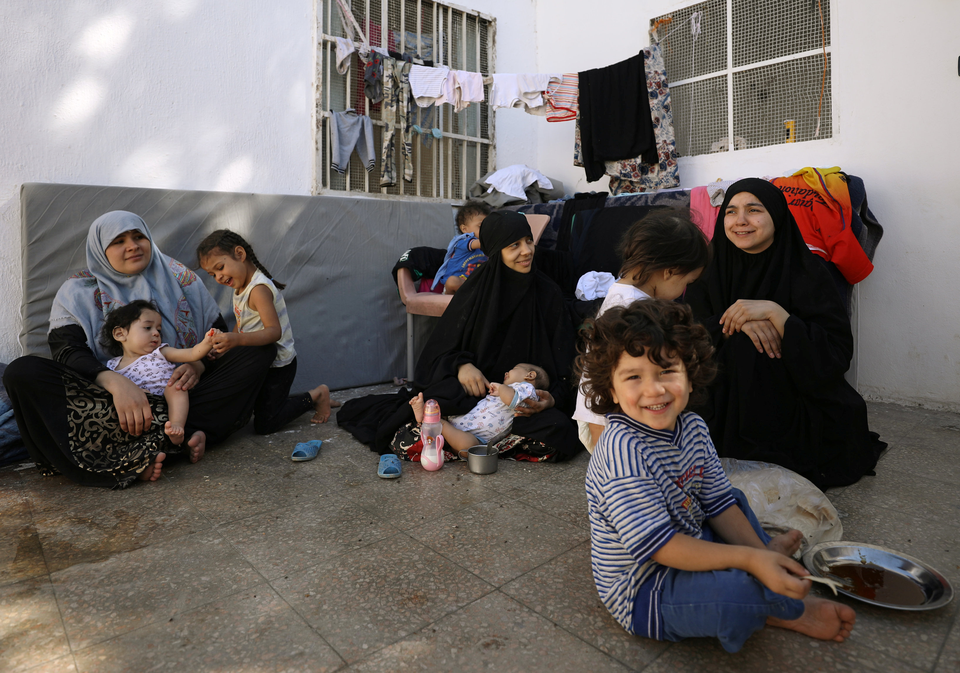 FILE - From left, Tunisians Khadouja al-Humri, Iman Othman and Lebanese Nour al-Huda, wives of former Islamic State fighters, sit with their children at a camp for displaced people in Ain Issa, north of Raqqa, Syria, June 21, 2017.