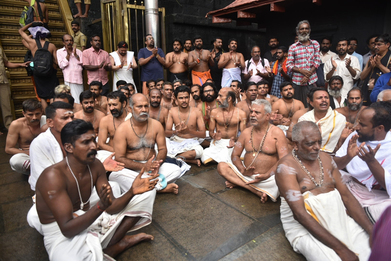 Hindu priests and temple staff sit on a protest against a ruling from India's top court to let women of menstruating age entering Sabarimala temple, one of the world's largest Hindu pilgrimage sites, in the southern Indian state of Kerala, Friday, Oc...