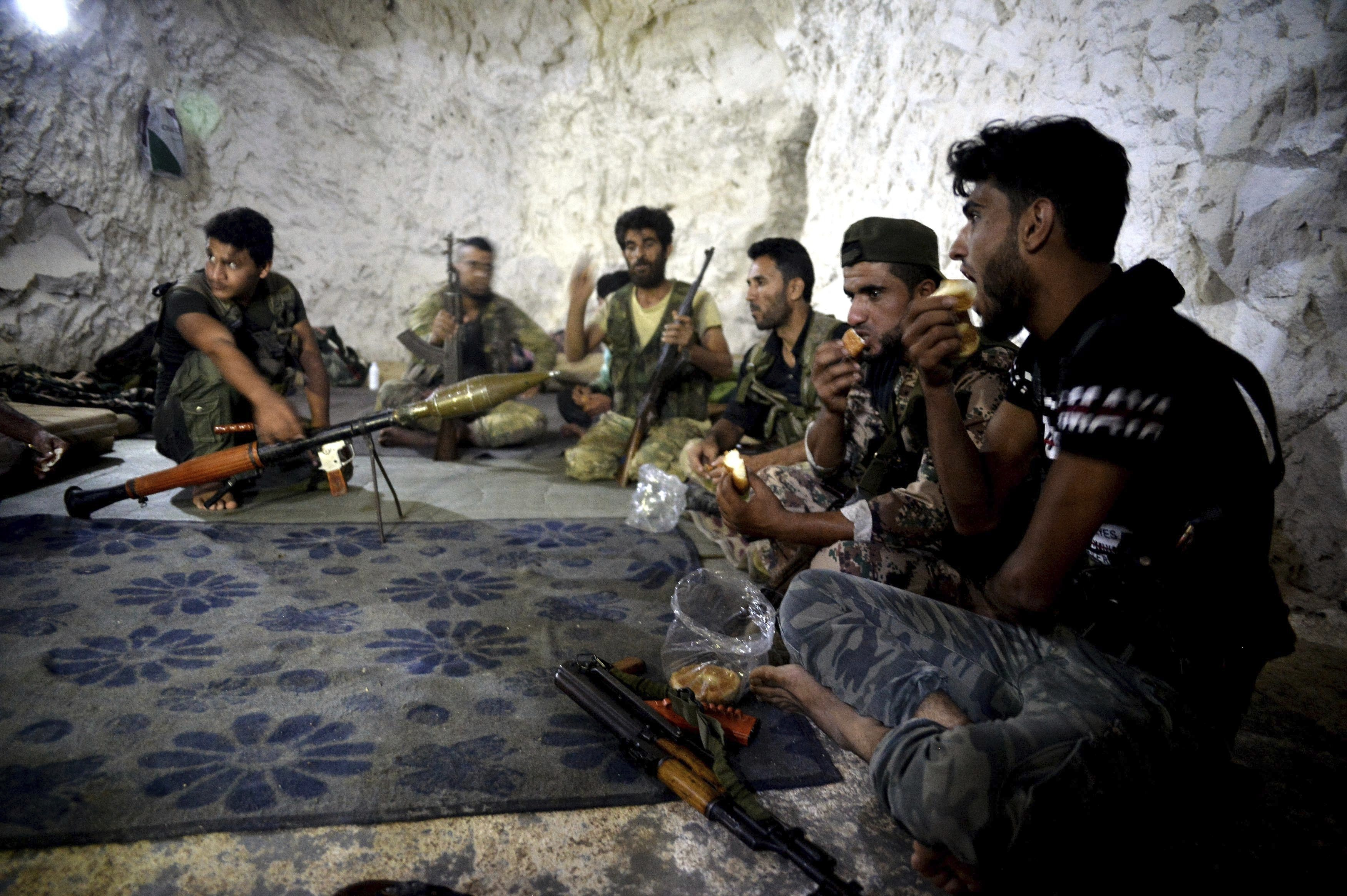 FILE - Syrian rebels eat in a cave in which they also live, on the outskirts of the northern town of Jisr al-Shughur, Idlib province, Syria, west of the city of Idlib, Sept. 9, 2018.
