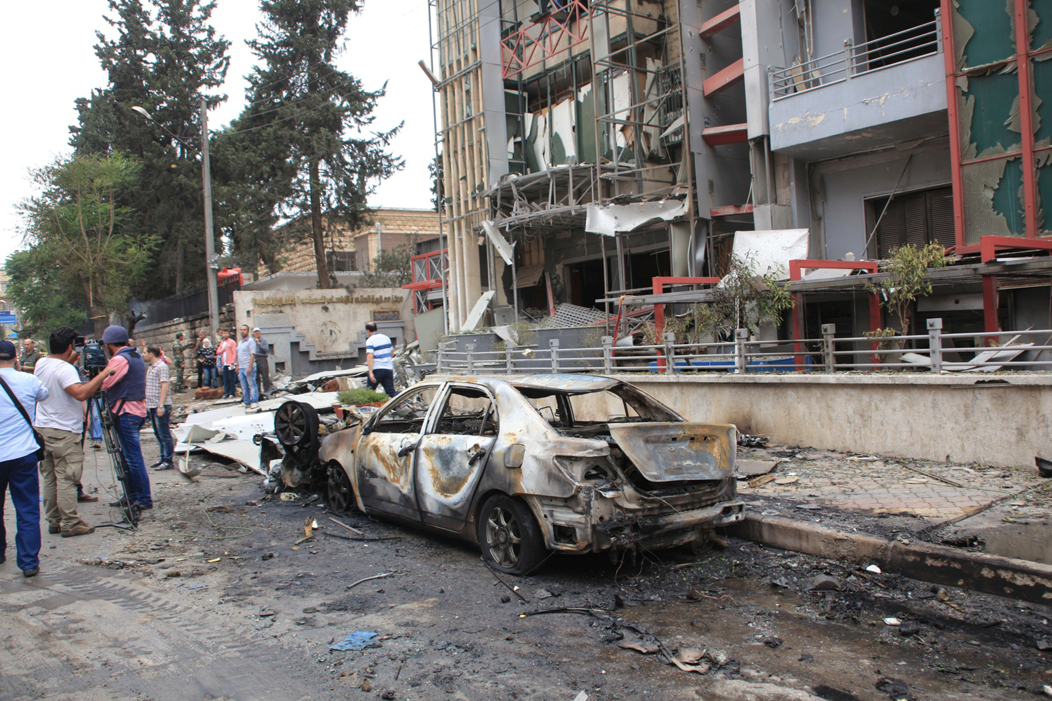 Journalists and civilians stand near the damage after rockets fired by insurgents hit the al-Dabit maternity clinic in government-held parts of Aleppo city, Syria, in this handout picture provided by SANA, May 3, 2016.