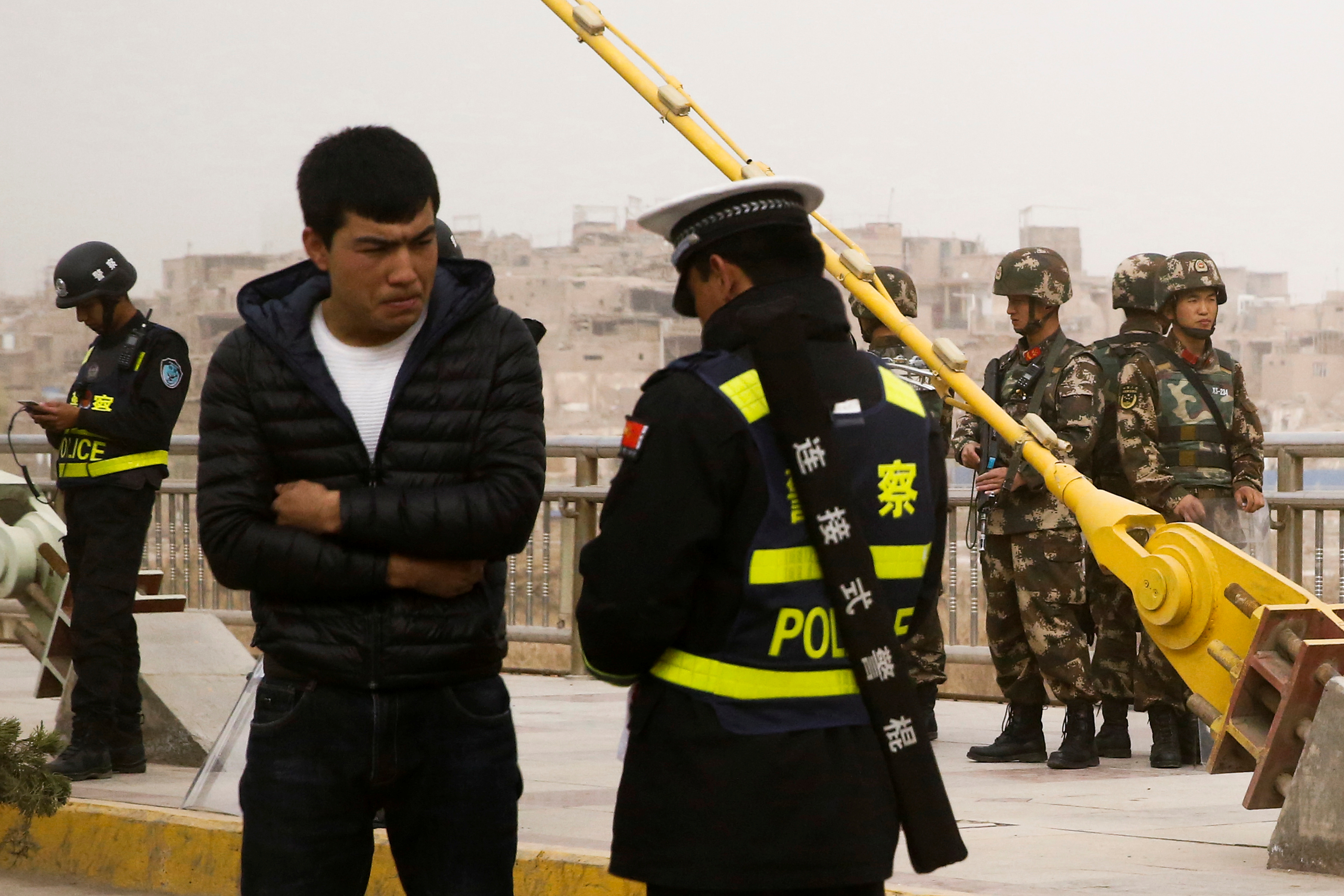 FILE - A police officer checks the identity card of a man as security forces keep watch in a street in Kashgar, Xinjiang Uighur Autonomous Region, China, March 24, 2017.