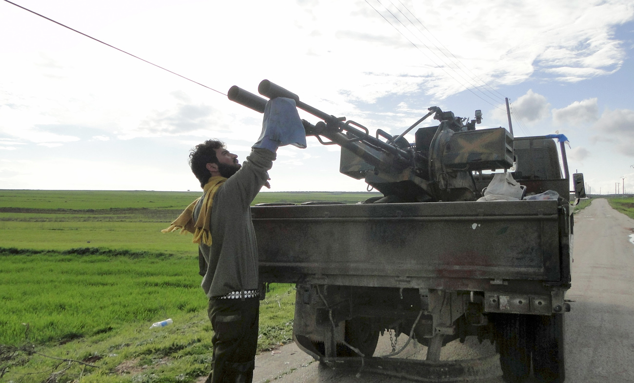 A Free Syrian Army fighter cleans an anti-aircraft artillery gun near the Menagh military airport in Aleppo's countryside February 17, 2013.