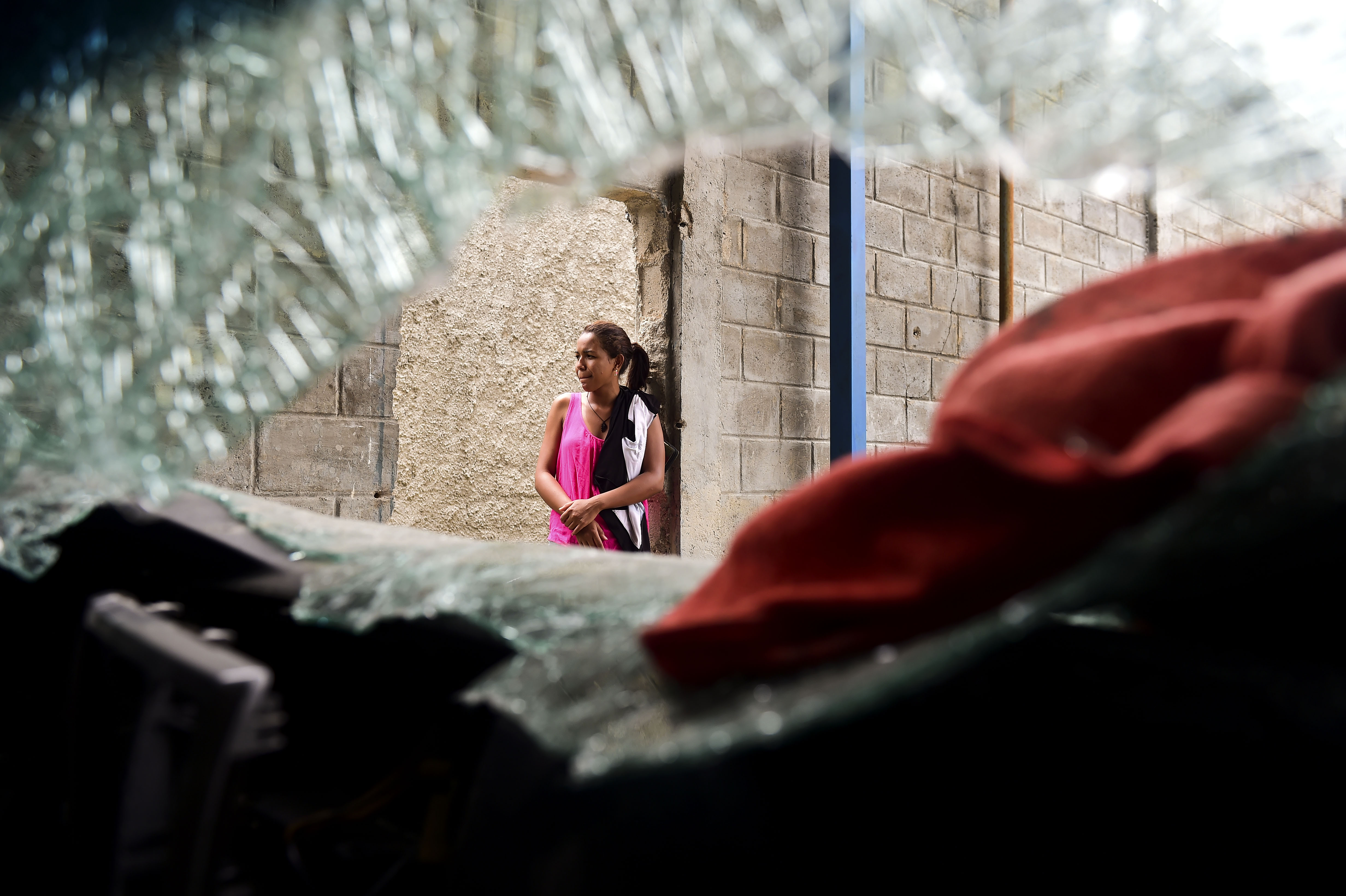A woman stands next to a damaged car at a supermarket parking bay in Valencia, Carabobo State, Venezuela, May 5, 2017, the day after anti-government protesters looted stores, set fire to cars and clashed with police.