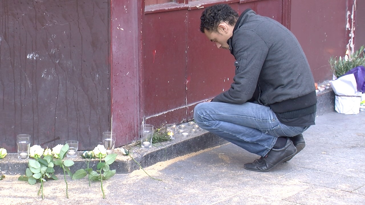 Man pays his respects to the victims of the terror attack at the Carillon bar in Paris, Nov. 15, 2015. (Photo: L. Bryant / VOA)