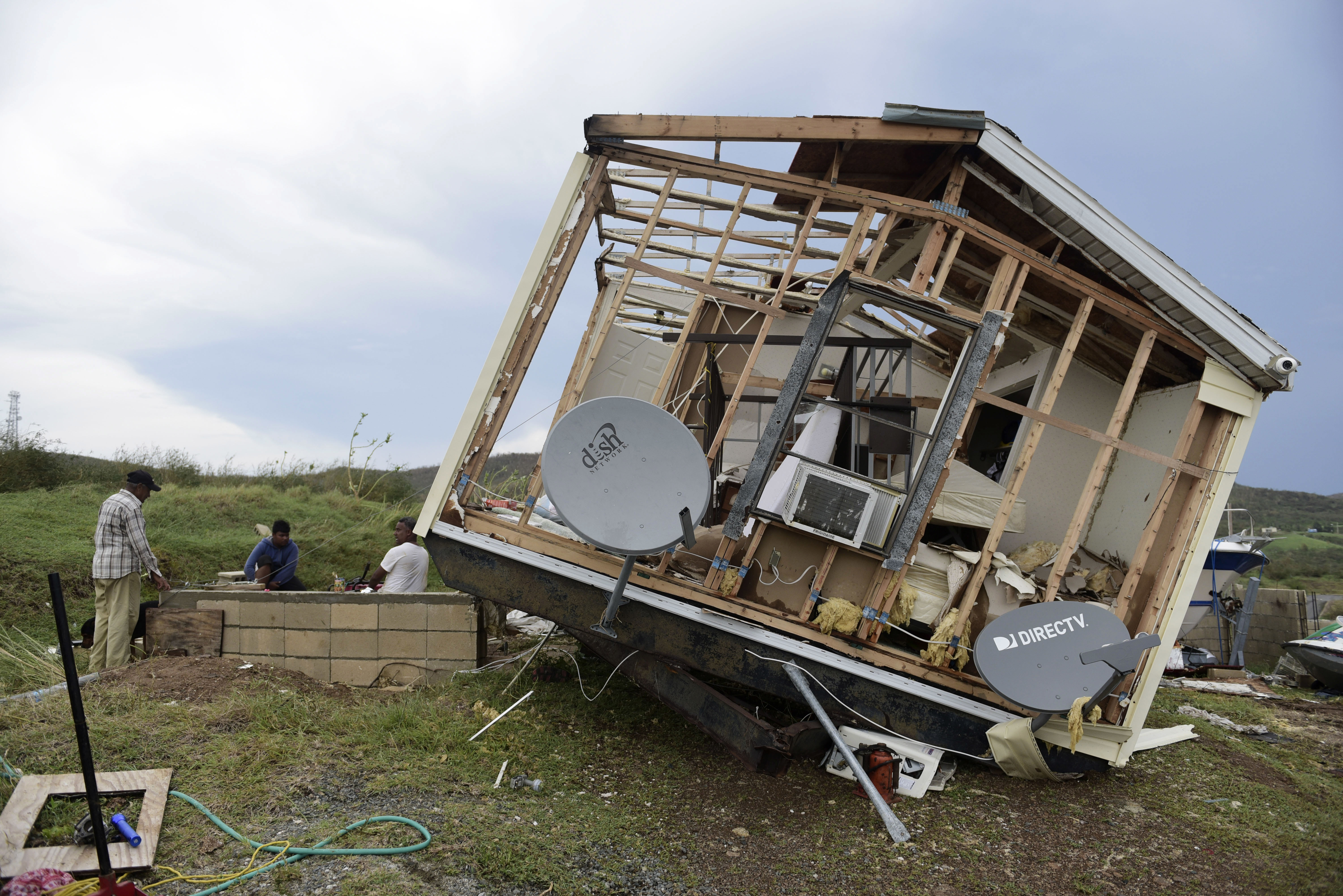 Juan Negron, right, prepares to start up a power generator in front of what's left of his damaged property, after the passage of Hurricane Irma, in the island of Culebra, Puerto Rico, Sept. 7, 2017.