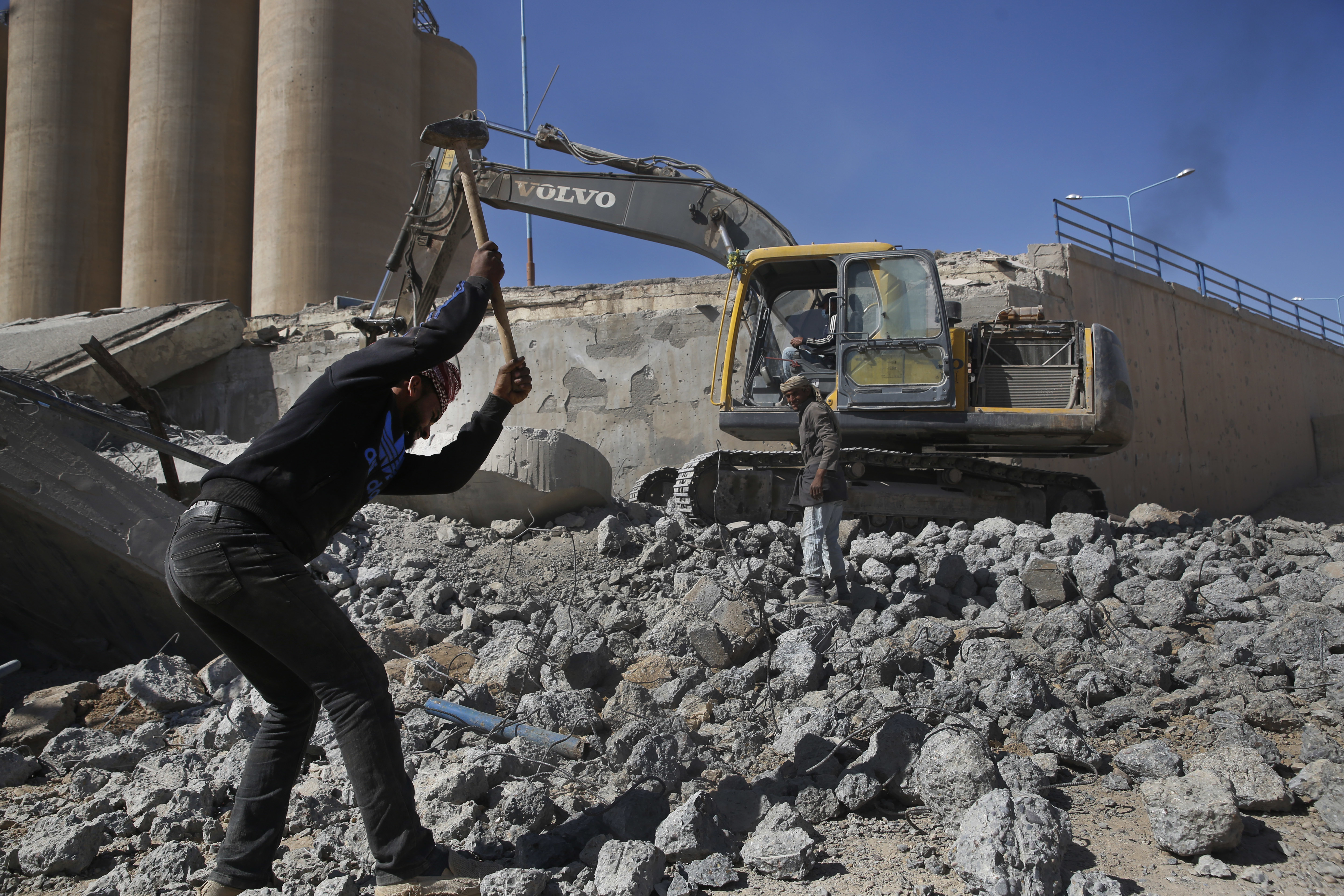 In this April 5, 2018 photo, workers remove rubble of a bridge that was destroyed last summer during fighting between U.S.-backed Syrian Democratic Forces fighters and Islamic State militants, in Raqqa, Syria.