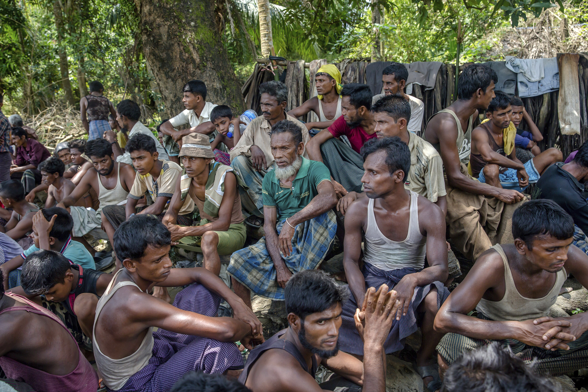 FILE - Rohingya Muslims from Myanmar wait to carry food items from Bangladesh's border toward a no man's land where they set up refugee camps in Tombru, Bangladesh, Sept. 15, 2017.