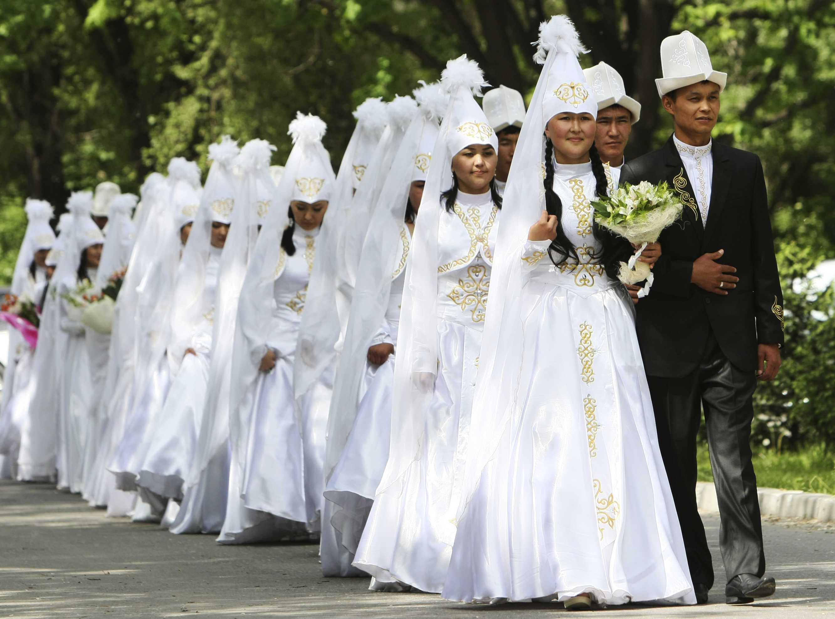 FILE - Brides and grooms leave after a mass wedding ceremony in the Kyrgyz capital of Bishkek, May 7, 2011. The wedding, held for 20 couples who could not afford their own celebrations, was sponsored by the Kyrgyz government.