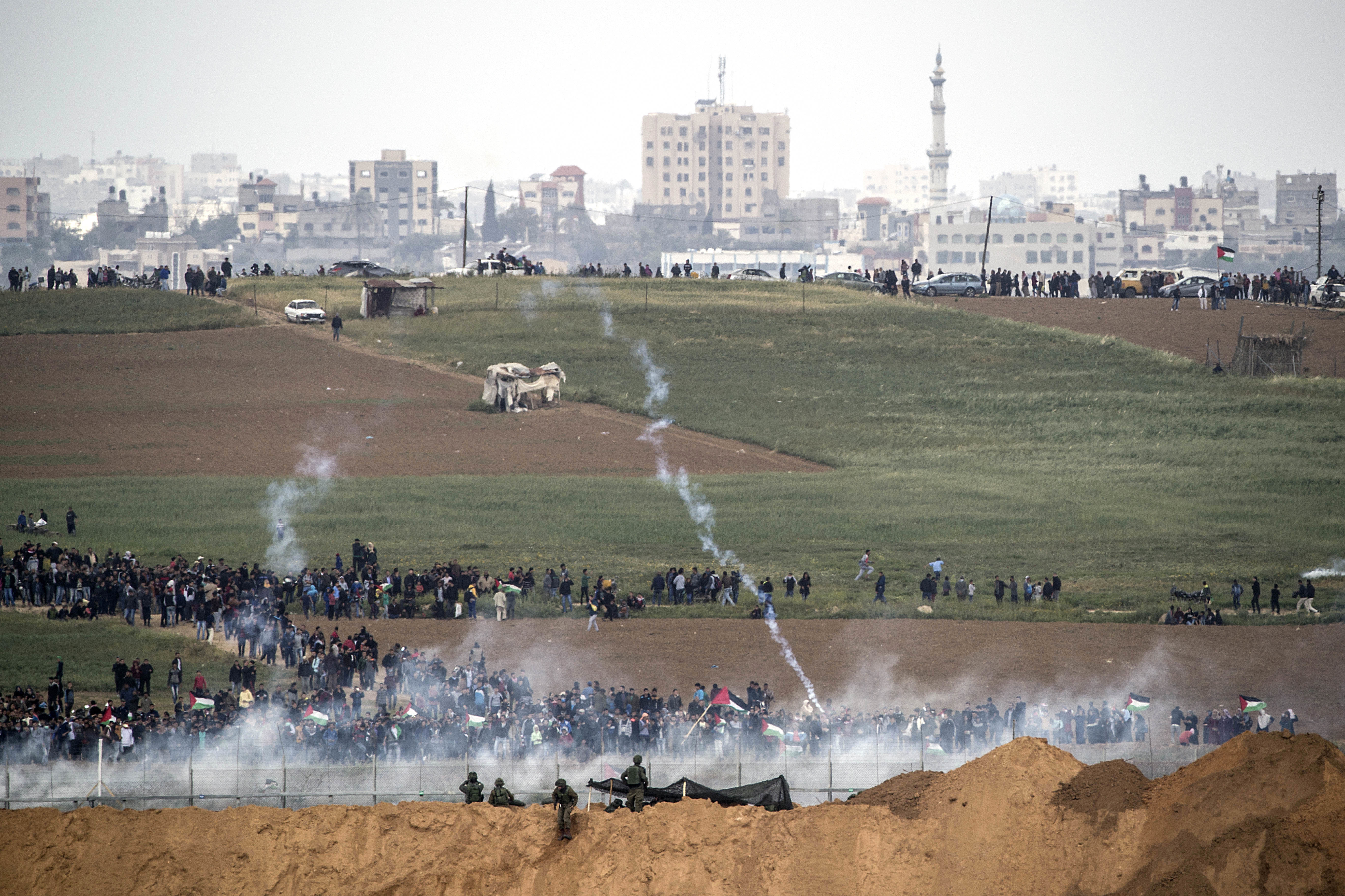 Israeli soldiers shoot tear gas toward Palestinian protesters as they gather on the Israel Gaza border, March 30, 2018.
