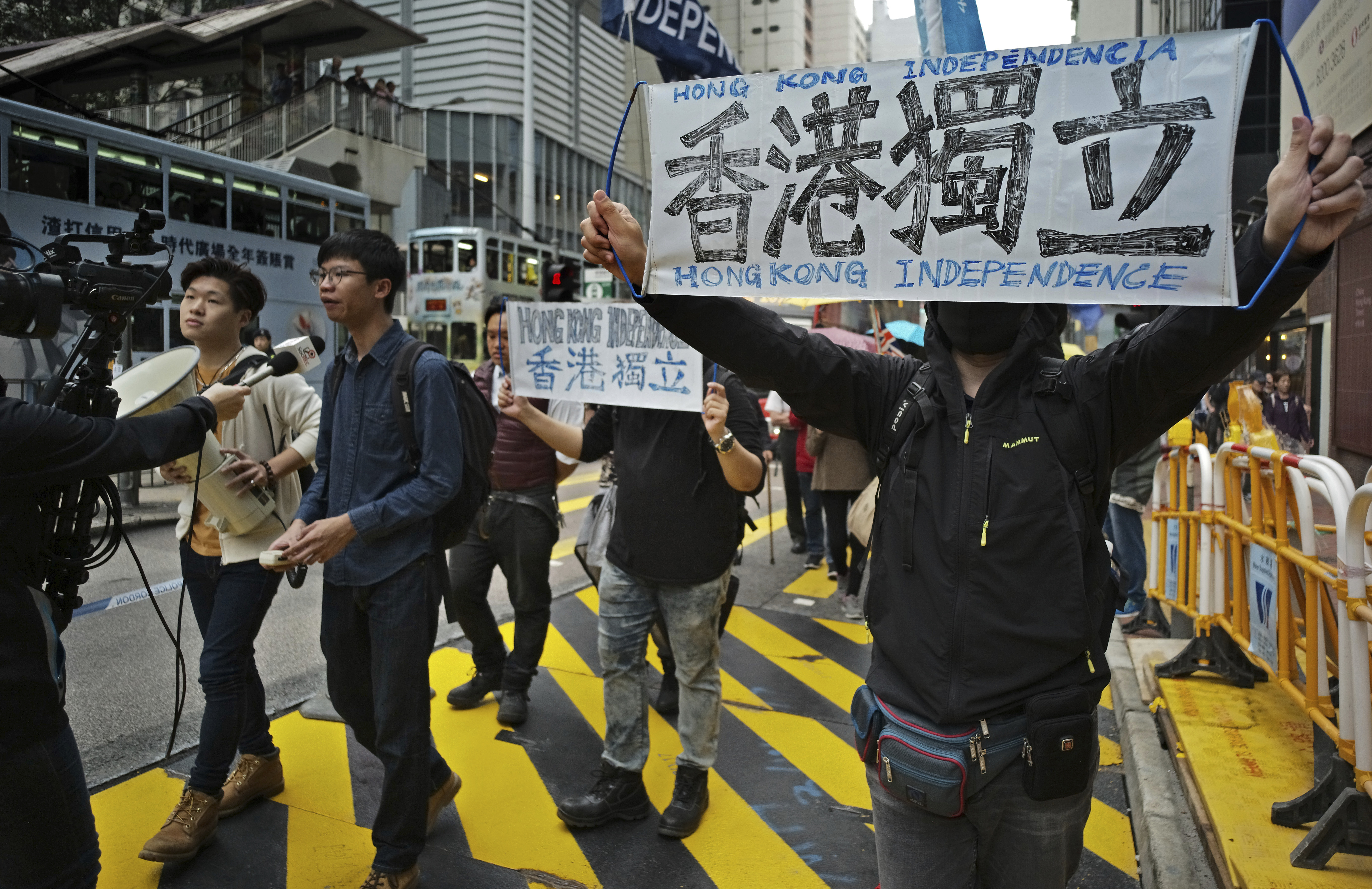 """FILE - Protesters against an extradition law hold banners reading """"Hong Kong Independence"""" during an anti-extradition law march toward government headquarters in Hong Kong, March 31, 2019."""