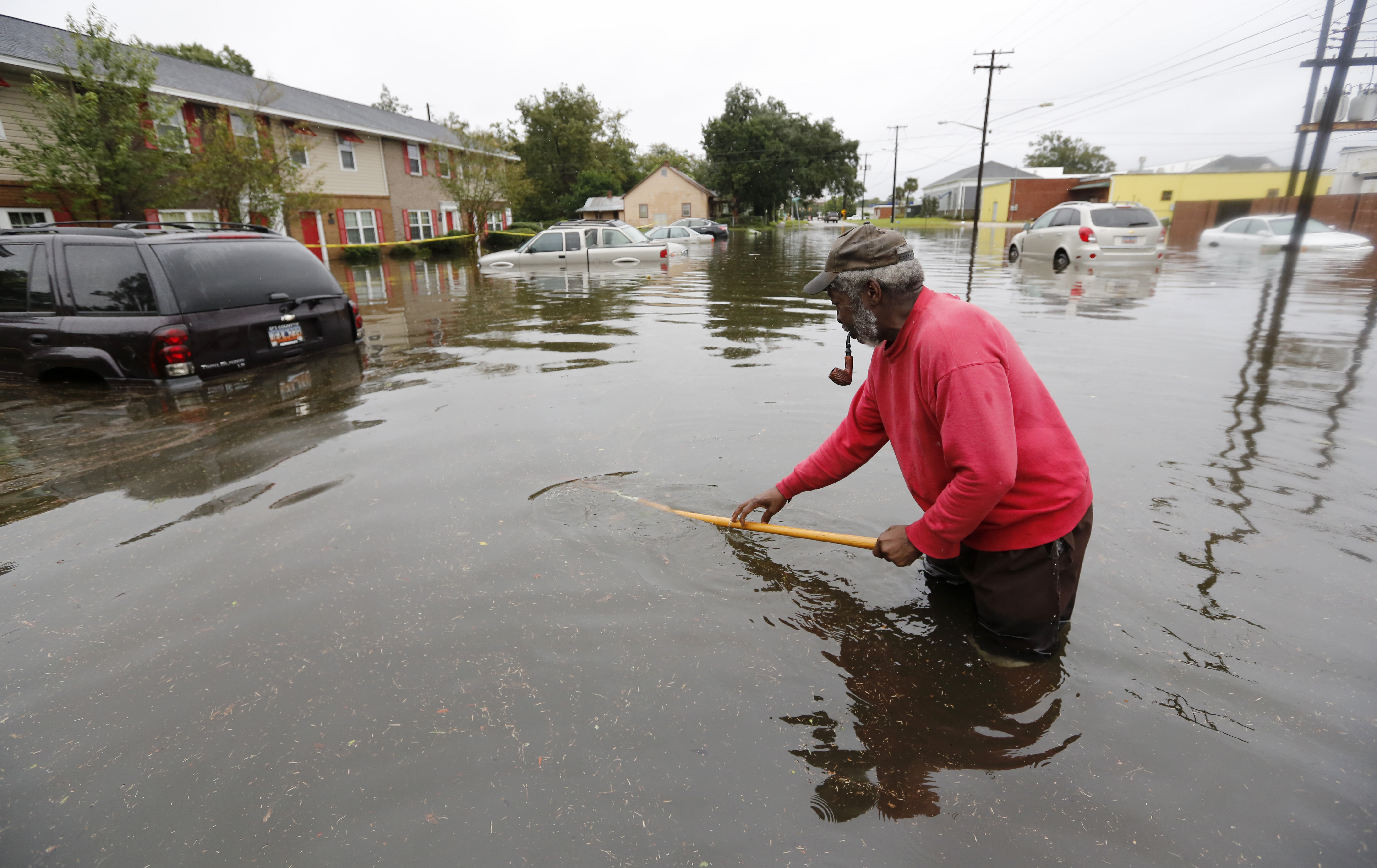 David Linnen takes a yard rake to clear drains in front of Winyah Apartments in Georgetown, S.C., Sunday, Oct. 4, 2015.