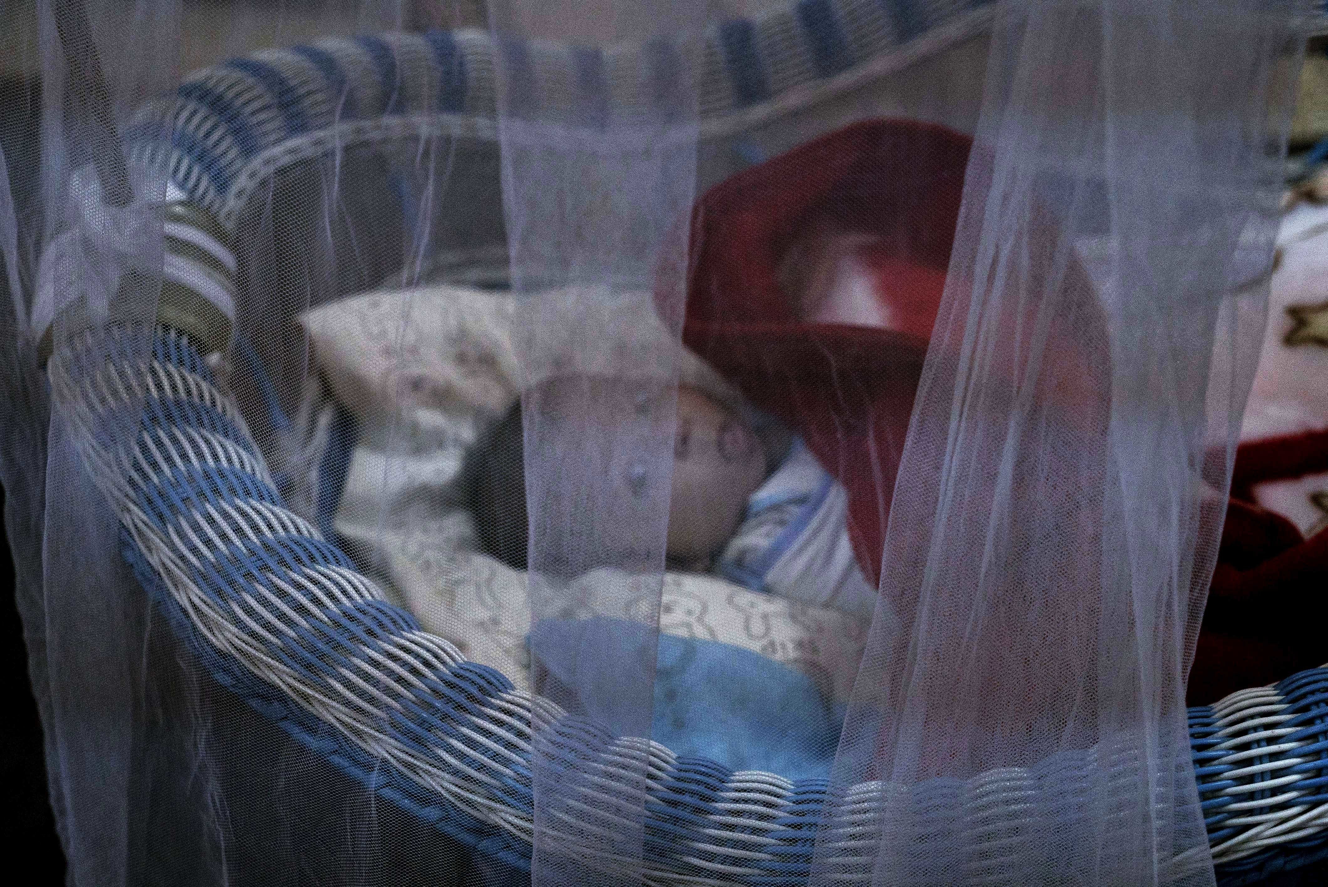 FILE - A newborn lies in her crib at the state-run al-Zuhour orphanage, in Mosul, Iraq, Aug. 19, 2018. Here, it's a mix of infants born to Iraqi women who were enslaved by militants and older children whose parents are jailed; some were simply abando...